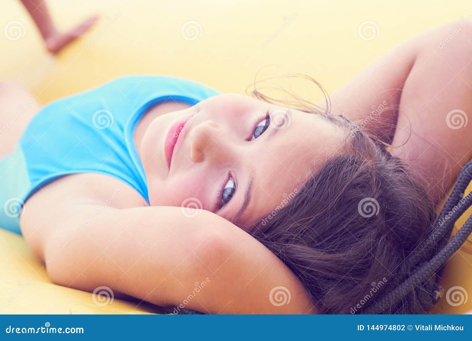 逗人喜爱的女孩放松的说谎在可膨胀的床垫特写镜头画象