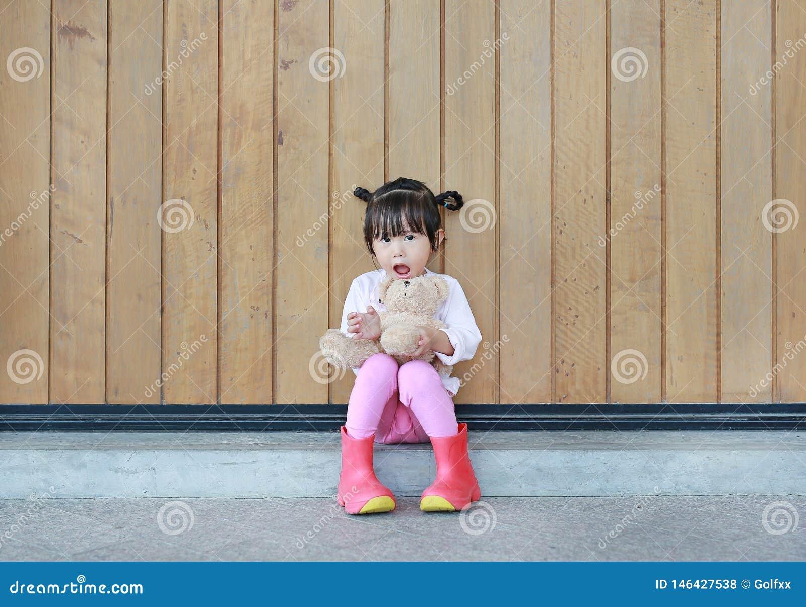 逗人喜爱的女孩画象坐和拥抱玩具熊对木板条墙壁
