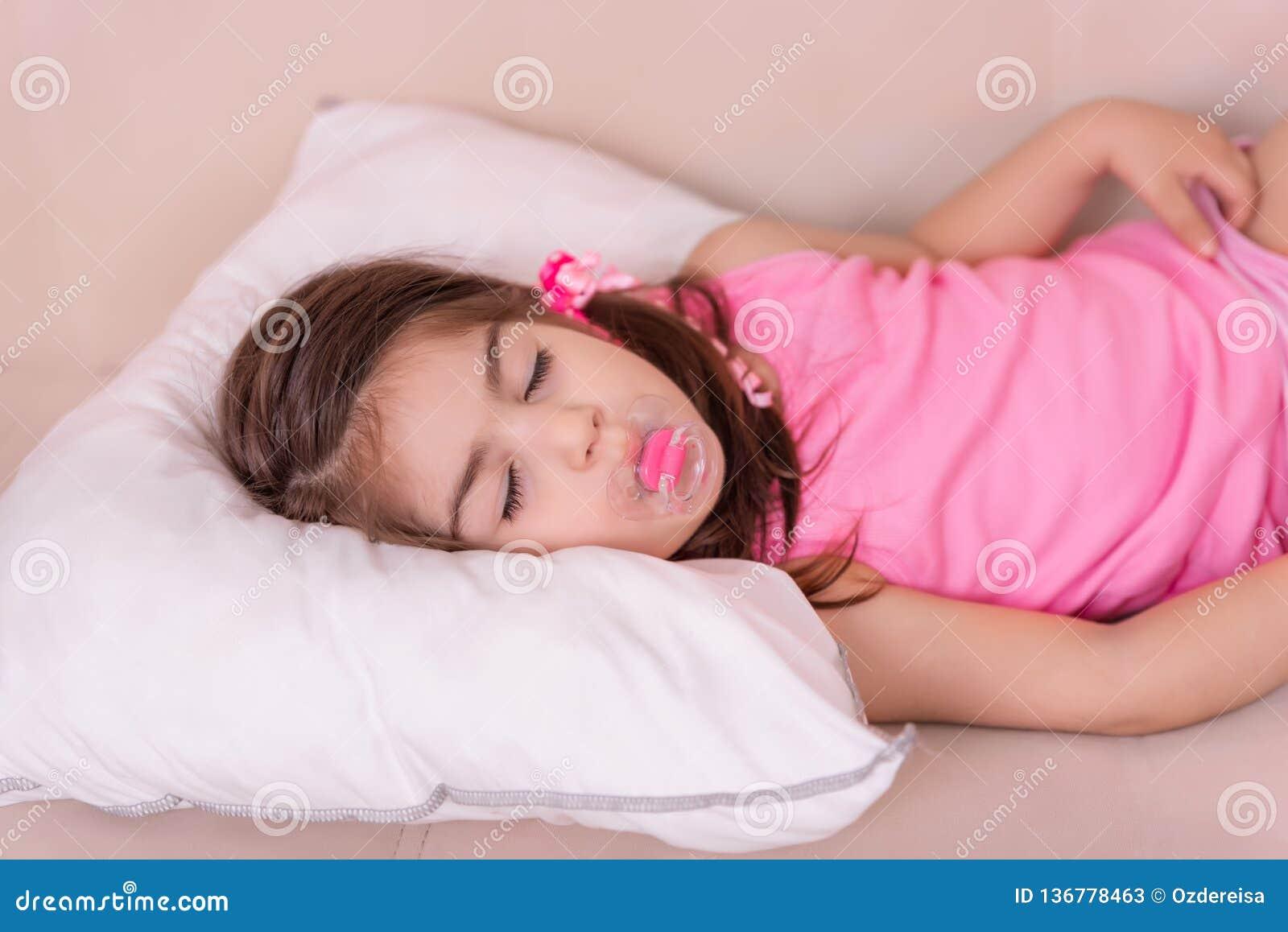 逗人喜爱的女孩睡眠画象在一张床上的与
