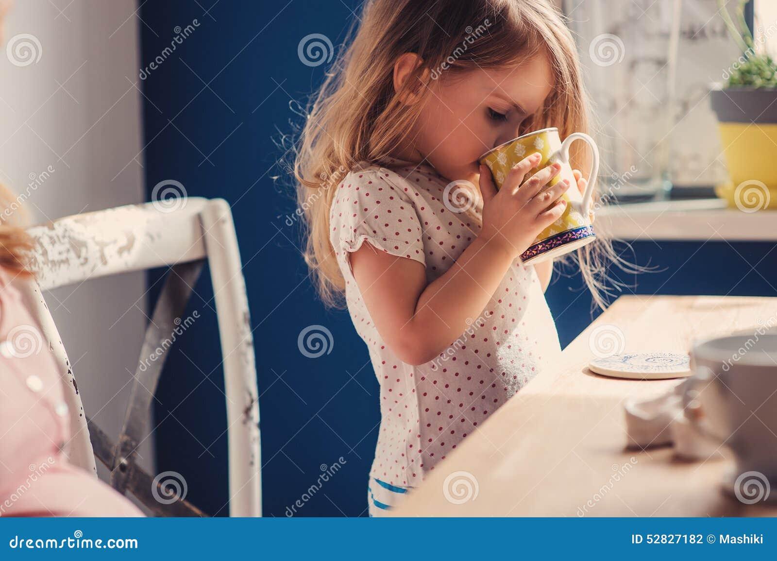 逗人喜爱的女婴饮用的茶早餐在晴朗的厨房里