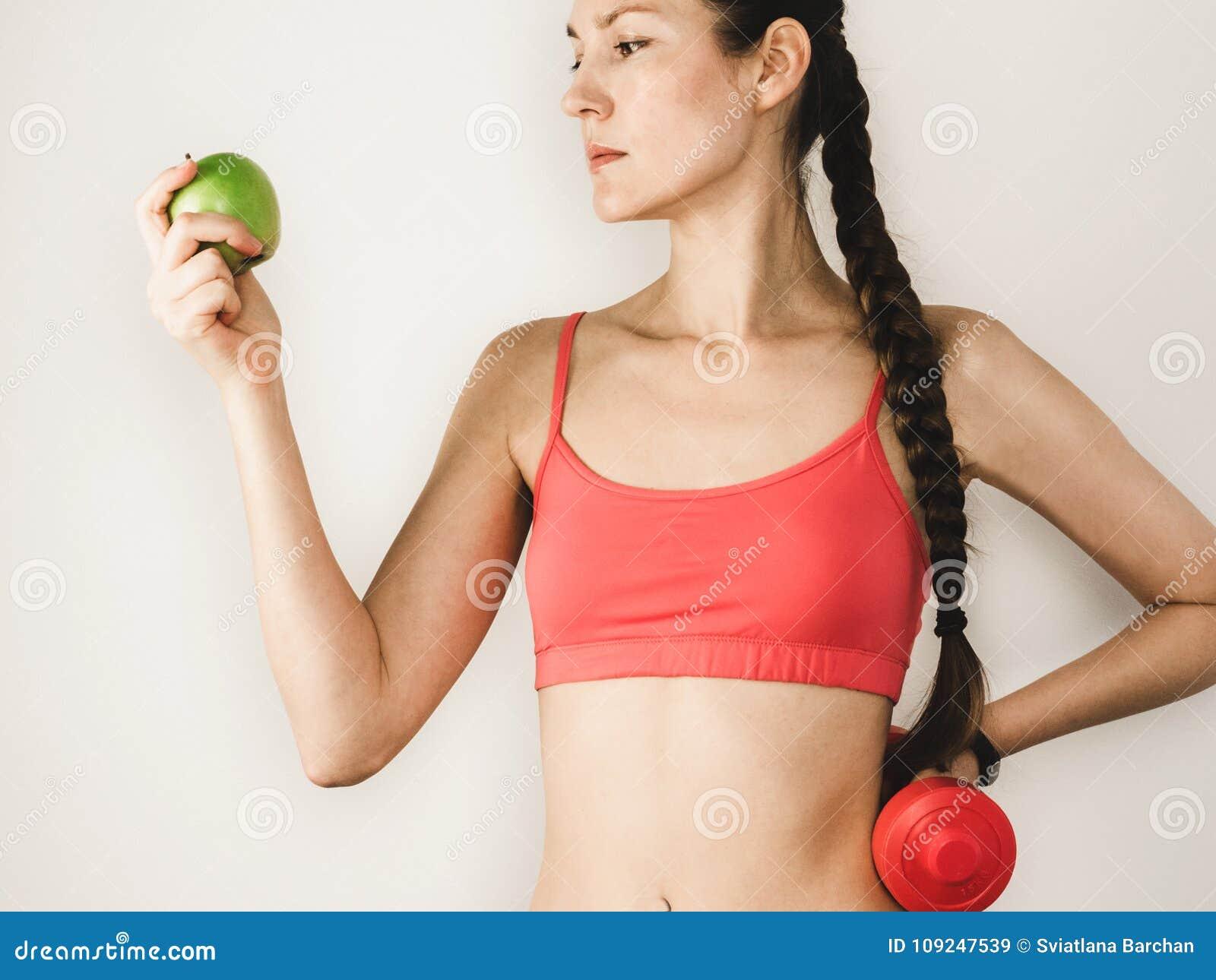 逗人喜爱的妇女用在训练期间的苹果与哑铃