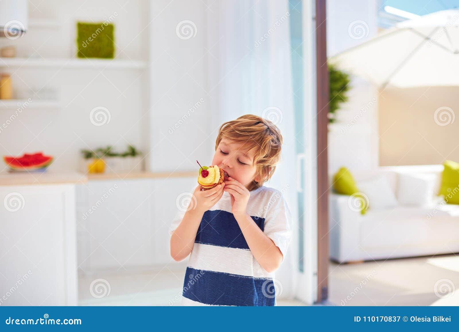 逗人喜爱的孩子,在家吃与被鞭打的奶油和果子的年轻男孩鲜美杯形蛋糕