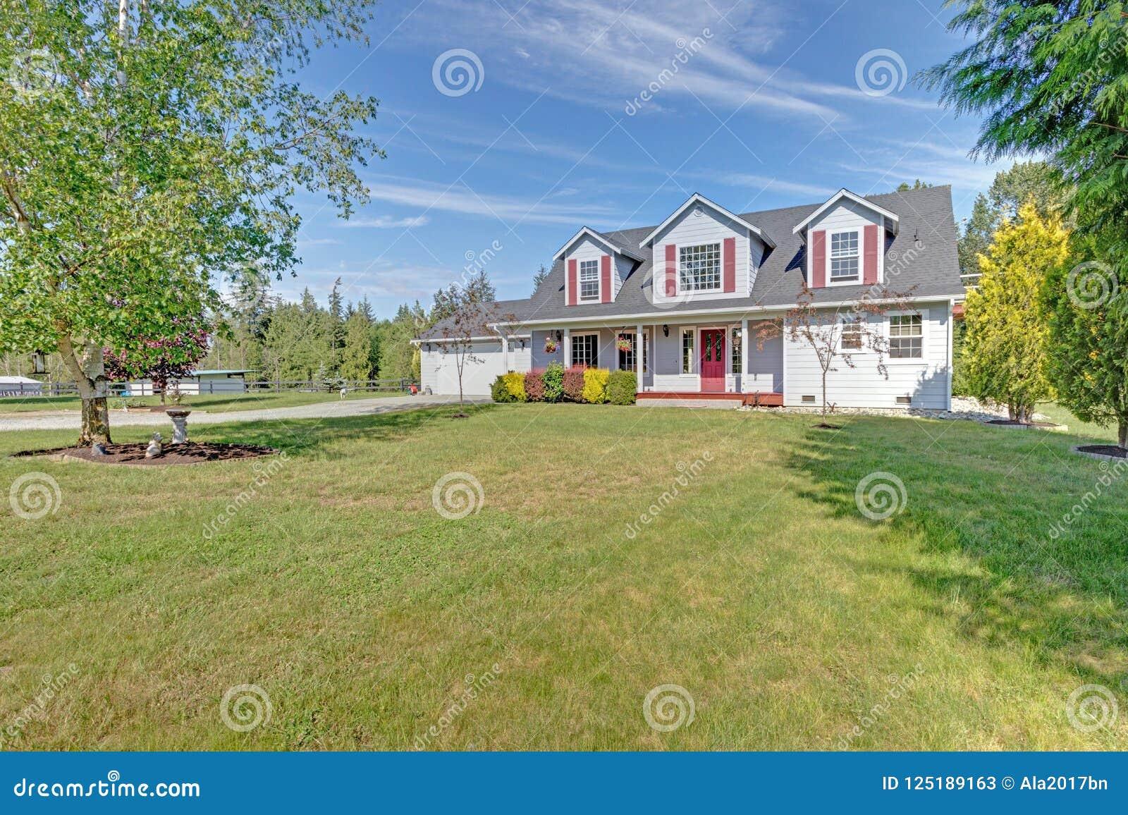 逗人喜爱的家外部与红色快门在一个夏日