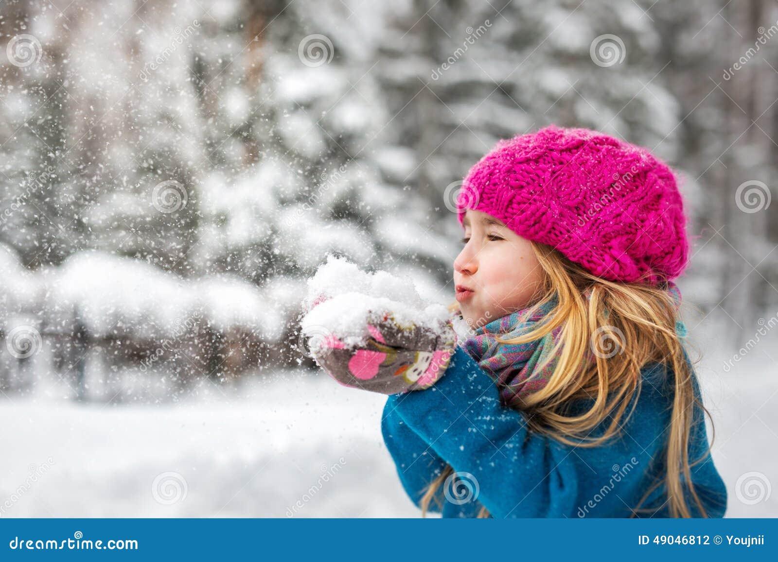 逗人喜爱的小女孩吹从手的雪