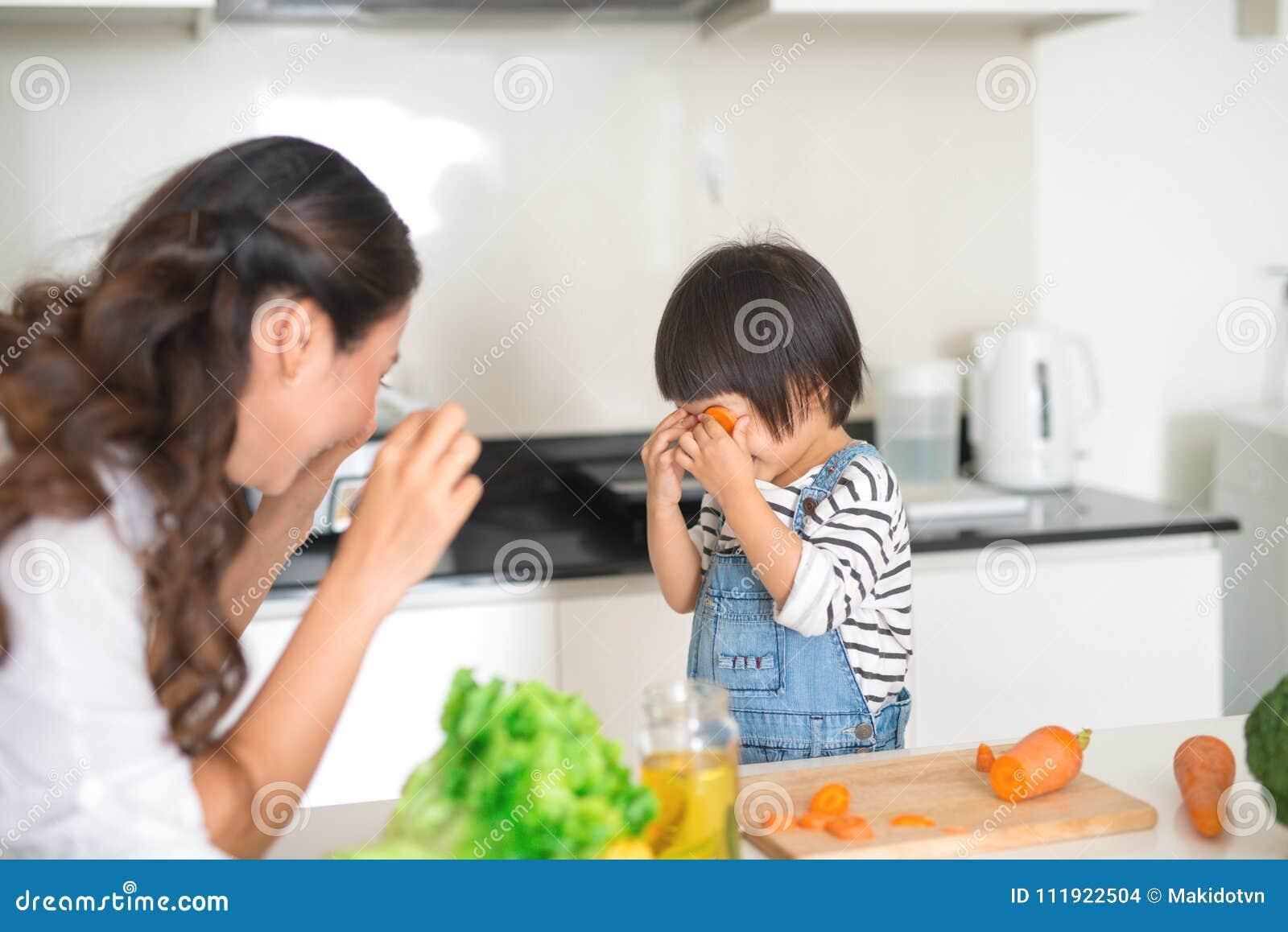 逗人喜爱的小女孩和她美丽的母亲饮用奶和eati