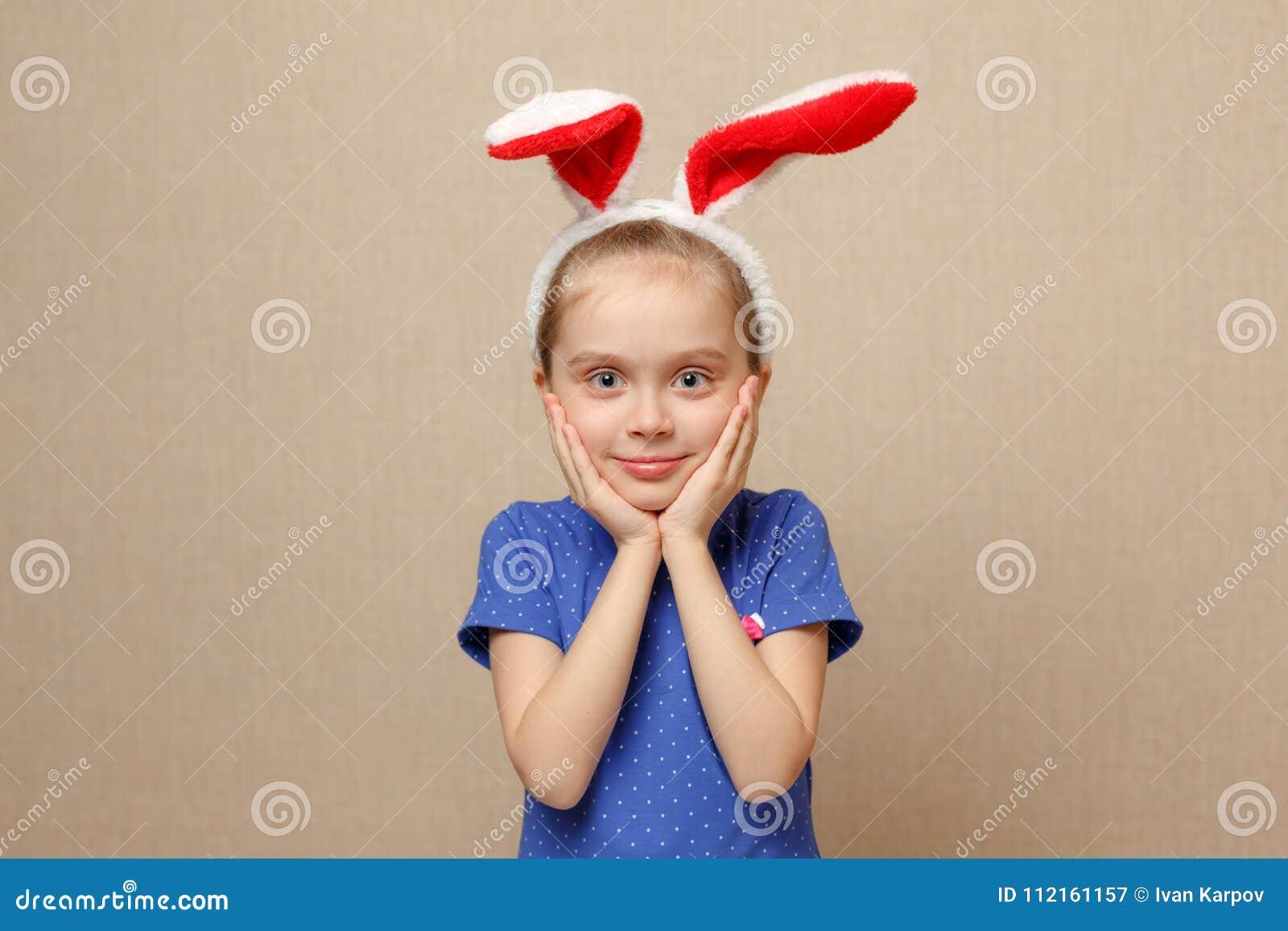 逗人喜爱的小孩女孩佩带的兔宝宝耳朵在复活节天