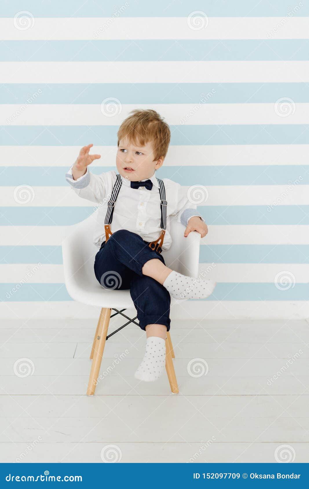 逗人喜爱的小男孩坐椅子生气的孩子