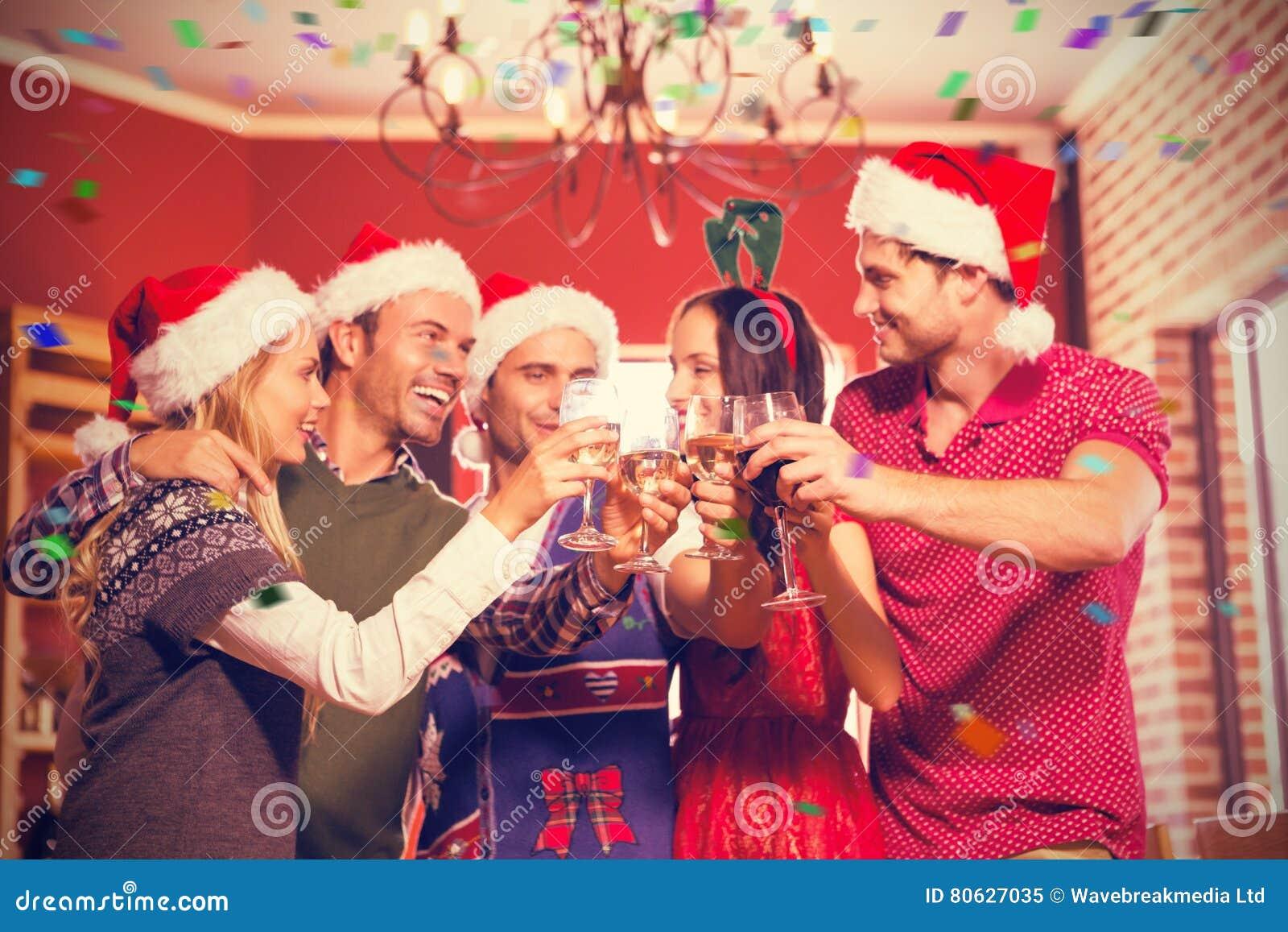 逗人喜爱的小组的综合图象敬酒与圣诞老人帽子的朋友