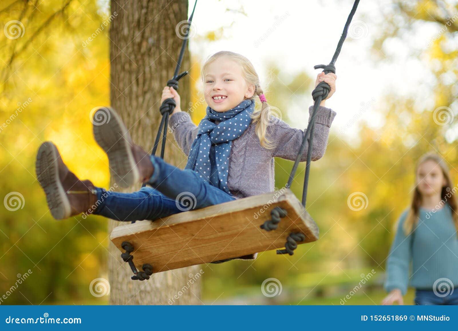 逗人喜爱的少女获得在摇摆的乐趣在晴朗的秋天公园 家庭周末在城市