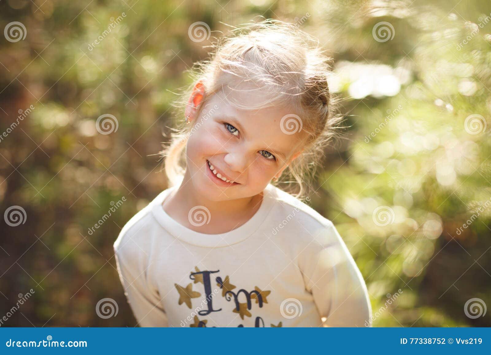 逗人喜爱的快乐的小女孩特写镜头画象在公园