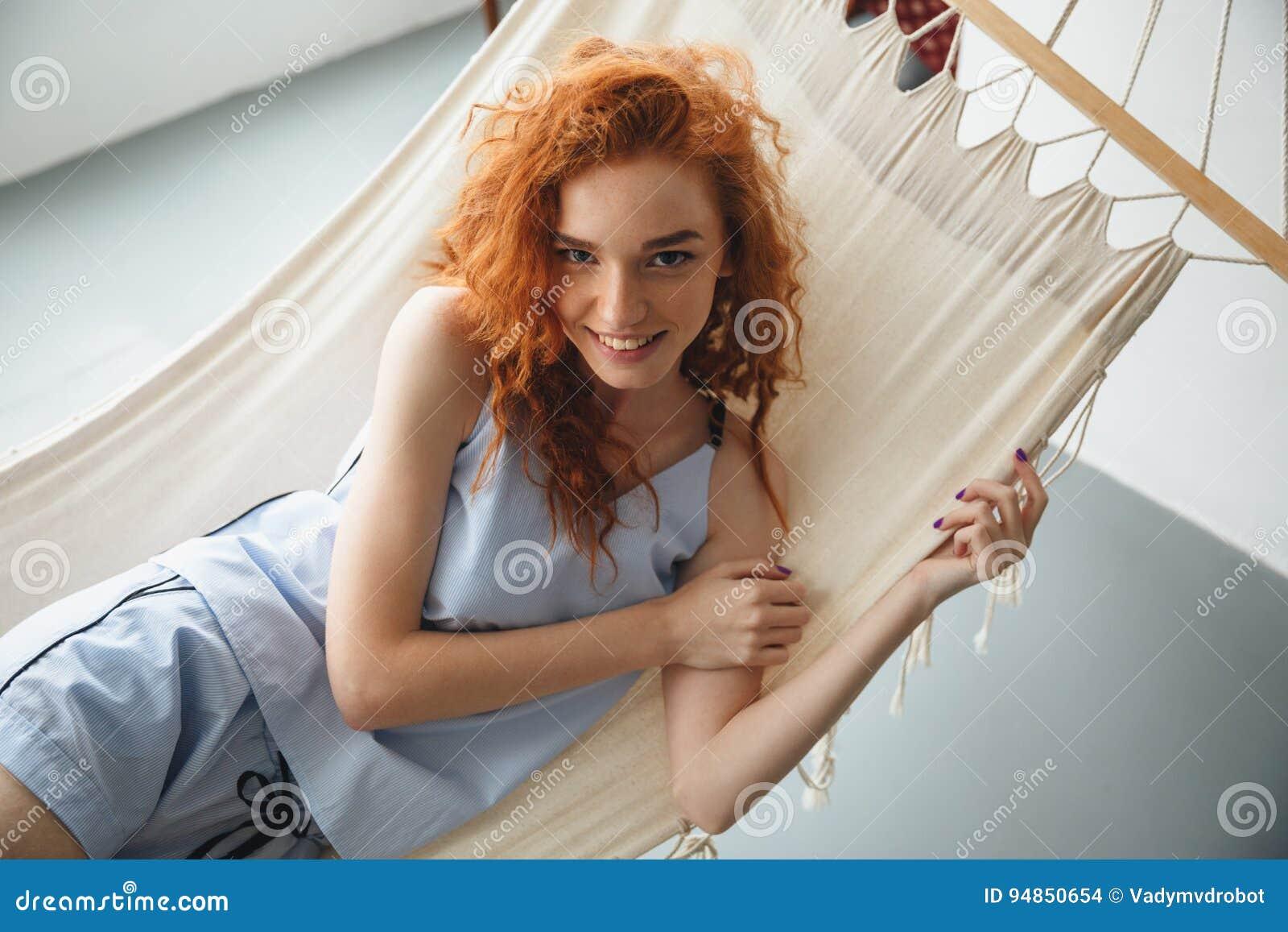 逗人喜爱的快乐的年轻红头发人夫人在吊床说谎