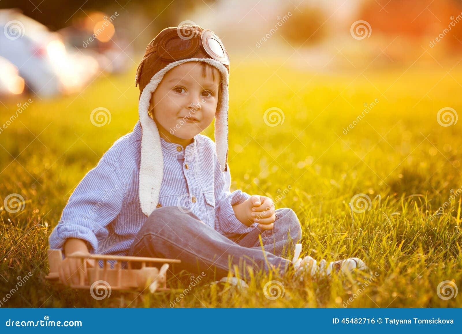 逗人喜爱的男孩,使用与在日落的飞机在公园