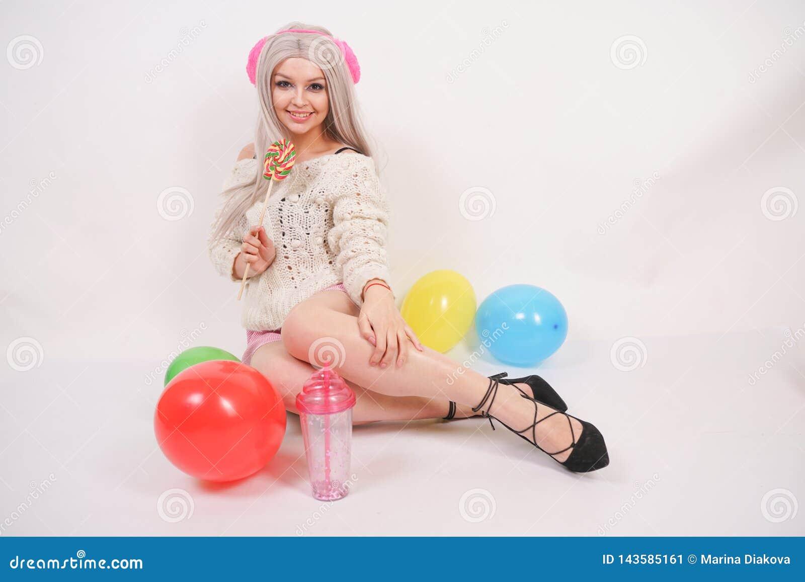 逗人喜爱的白肤金发的在乳状颜色被编织的毛线衣和滑稽的短裤打扮的白种人愉快的女孩,她坐单独白色地板与
