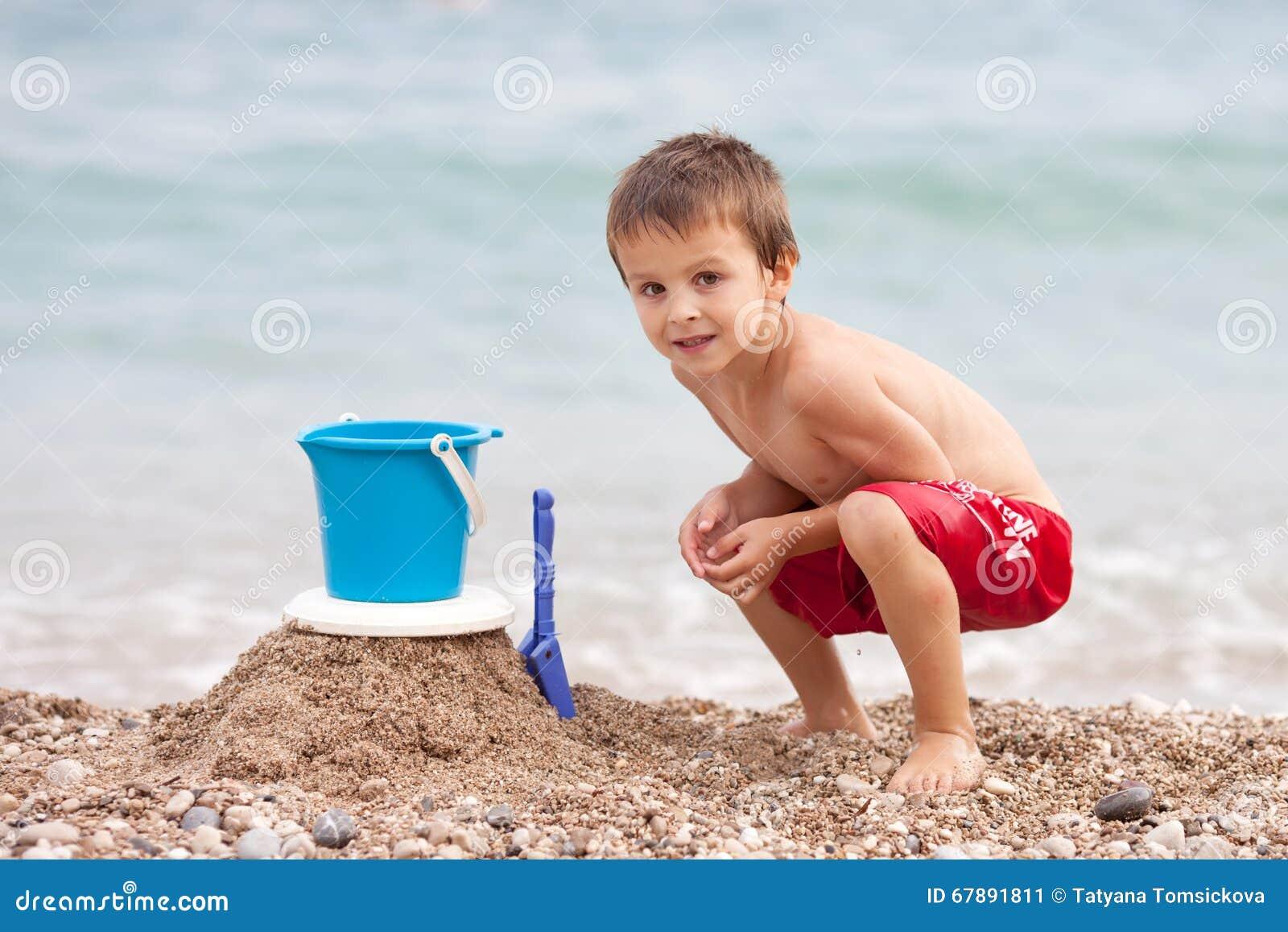 逗人喜爱的矮小的学龄前儿童男孩,使用在海滩wi的沙子