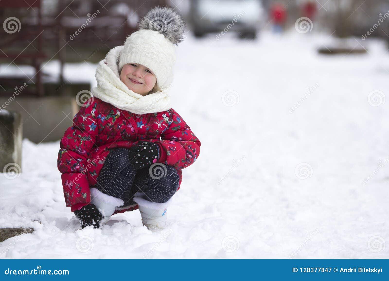 逗人喜爱的矮小的年轻滑稽的微笑的儿童女孩画象使用在雪的精密温暖的衣物的获得乐趣在丝毫的冬天冷的天
