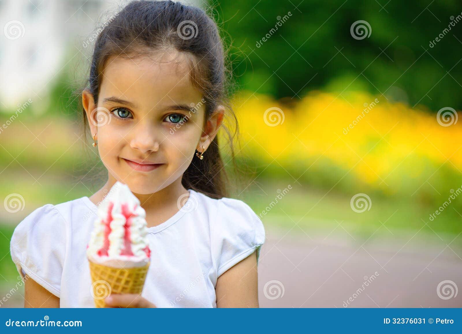 逗人喜爱的西班牙女孩用在公园的冰淇凌
