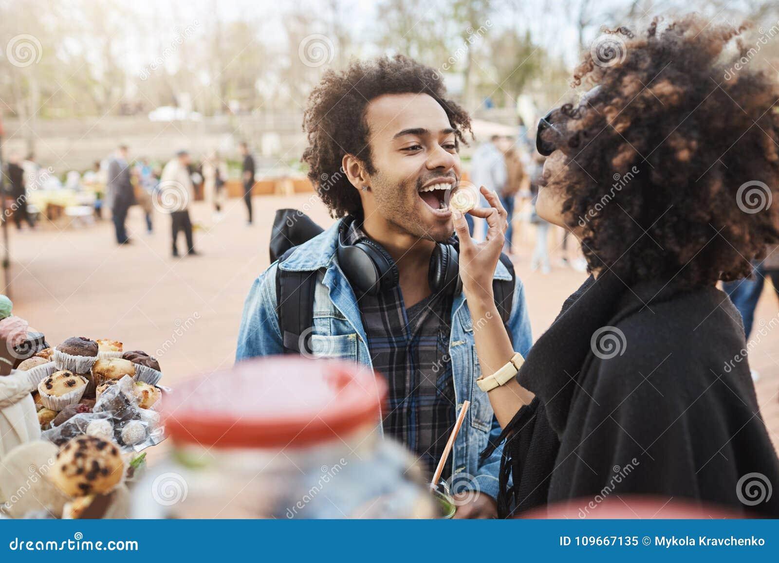 逗人喜爱的非裔美国人的夫妇边看法在爱的获得乐趣在公园在食物节日,站立的近的柜台期间和