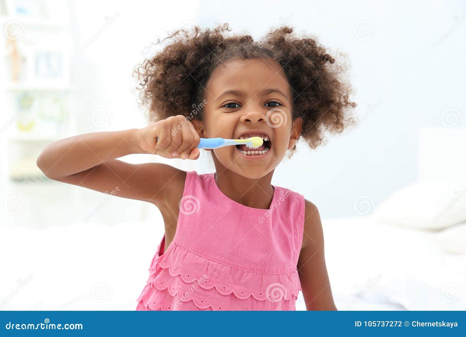 逗人喜爱的非裔美国人的女孩掠过的牙在卫生间里