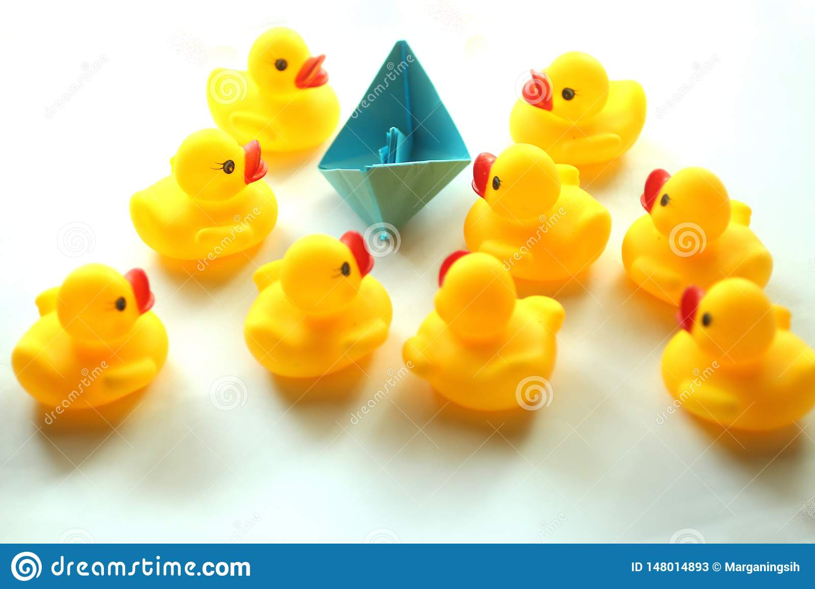 逗人喜爱的黄色橡胶鸭子和一条纸origami小船在蓝色