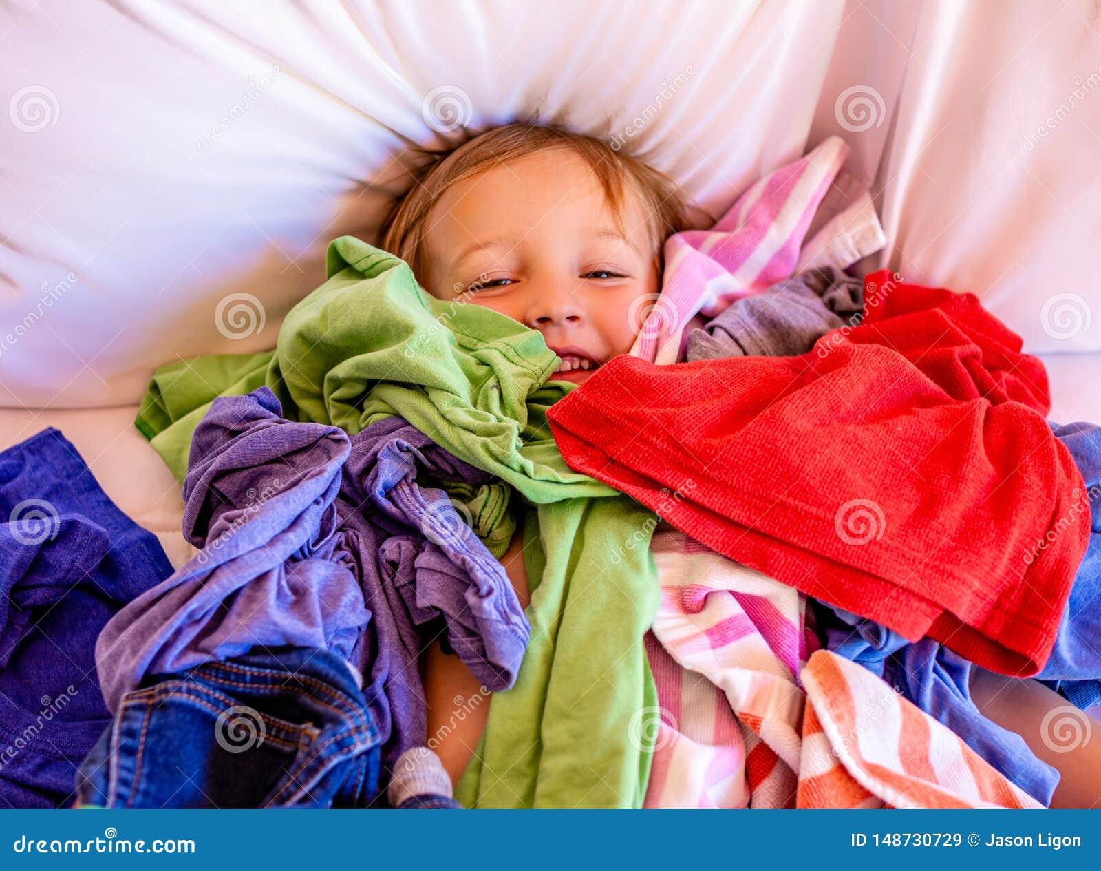逗人喜爱,可爱,微笑,放置在堆的白种人男孩肮脏的洗衣店在床