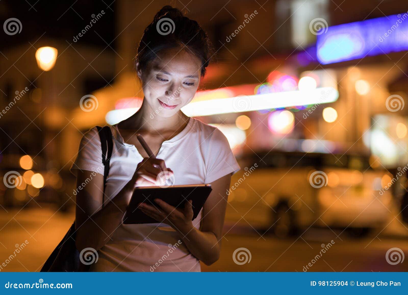 速写在数字式片剂计算机的妇女在晚上