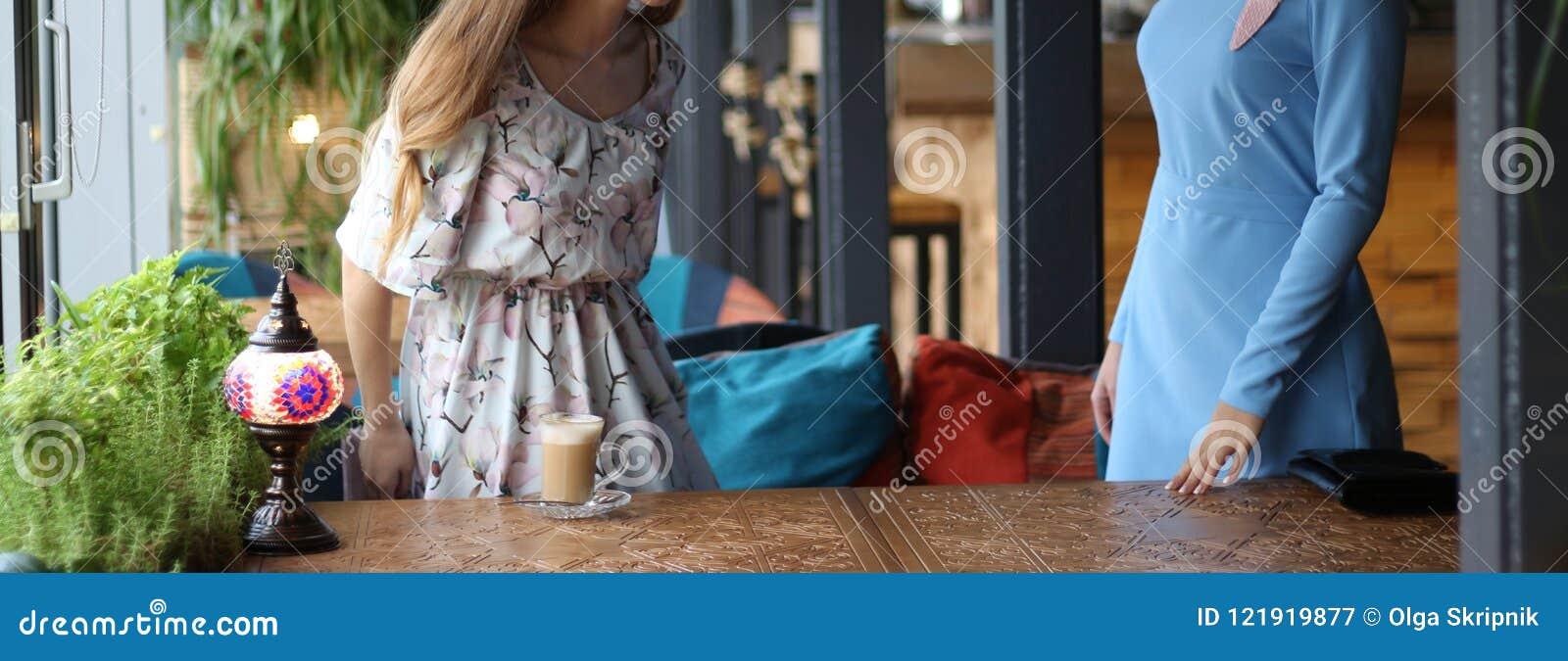 遇见一个咖啡馆的两名妇女咖啡的 被经受的一个人招呼第二 蓝色礼服,在花的礼服,在被雕刻的桌上是古芝