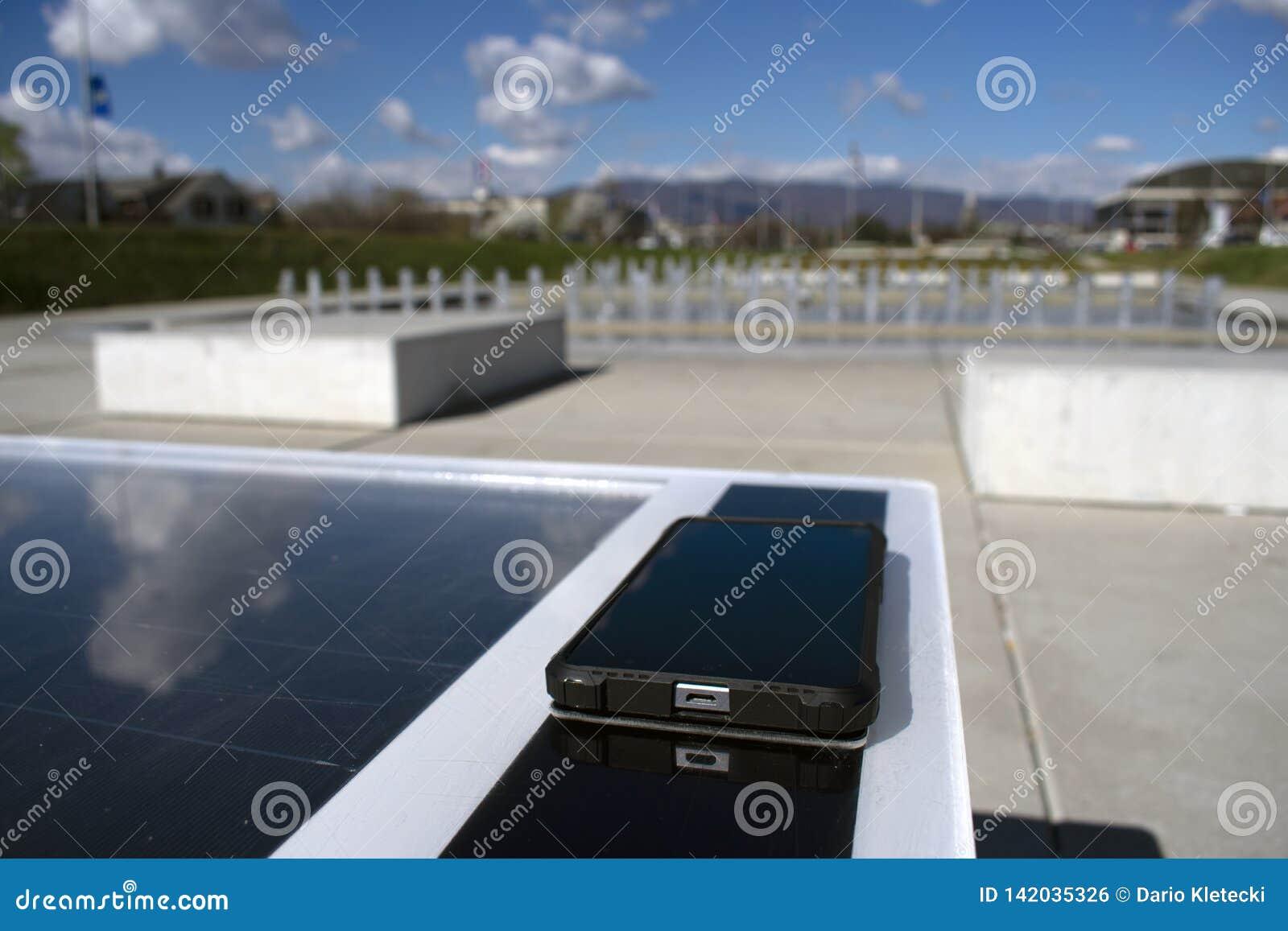 遥远地充电在太阳长凳的手机