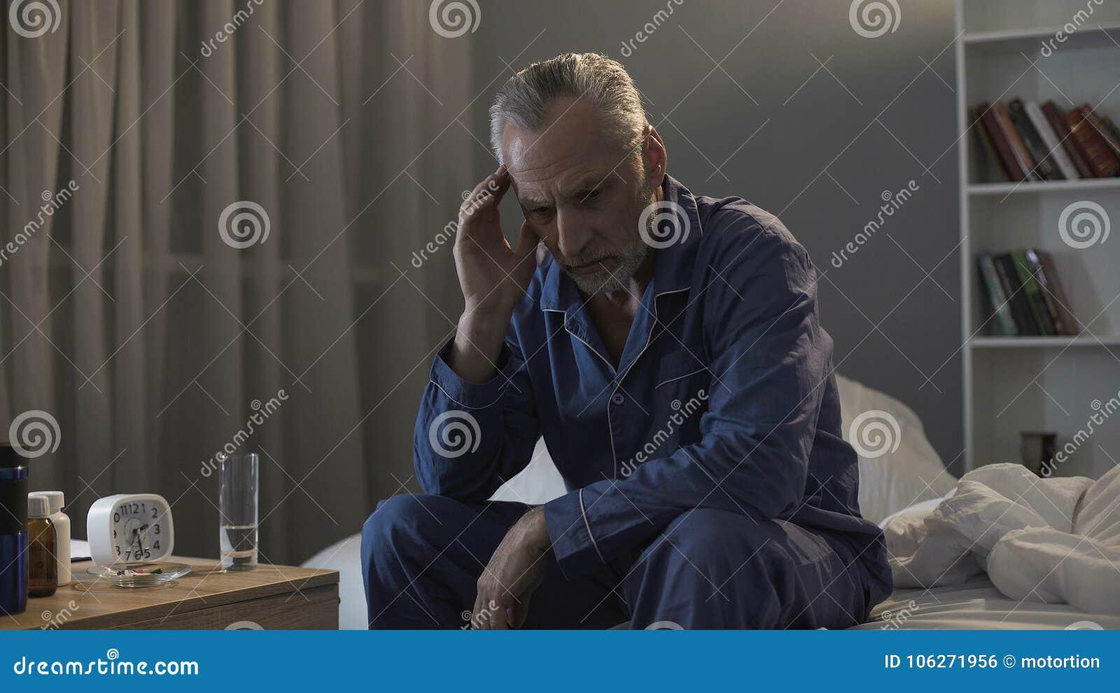 遭受头疼的失眠的老人,坐沙发在夜间