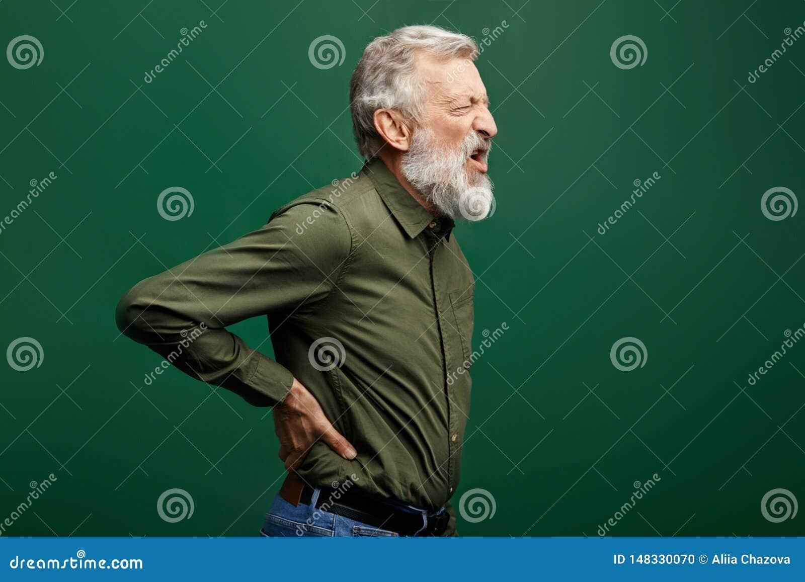 遭受背部疼痛的恼怒的呼喊的老人隔绝在绿色背景