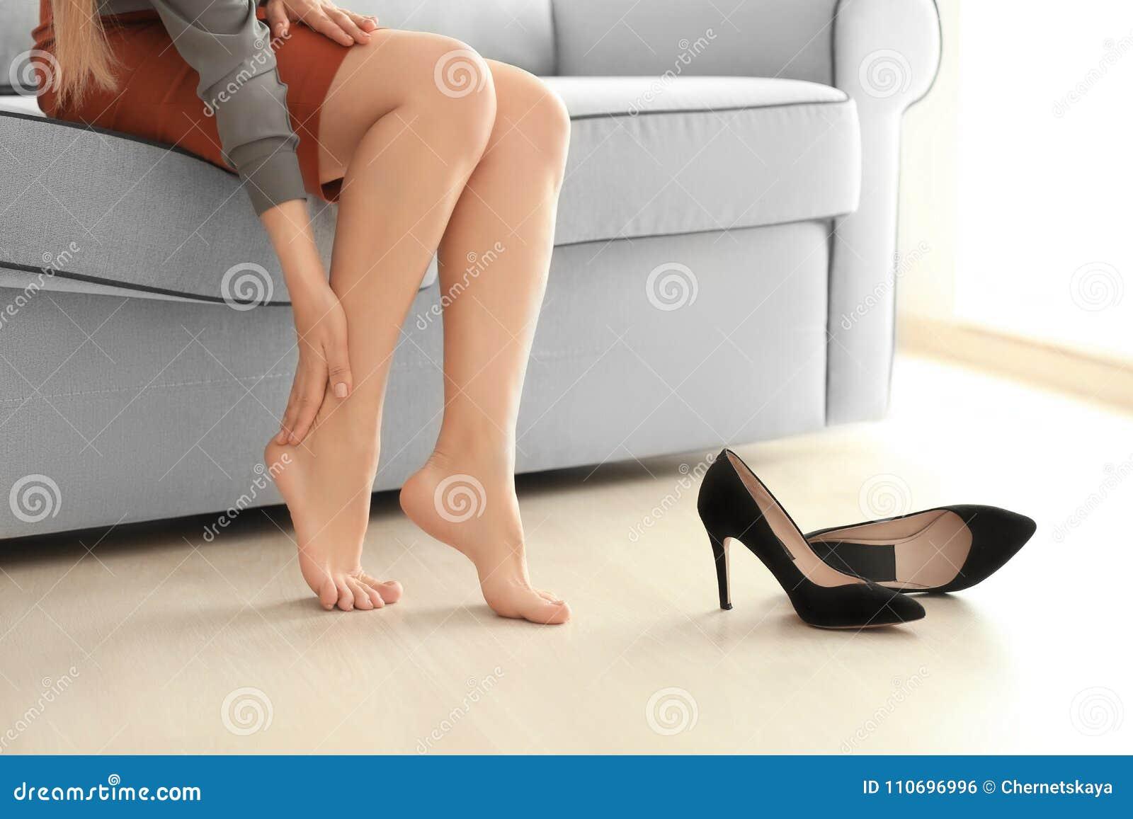 遭受腿痛的少妇由于难受的鞋子,当坐沙发时