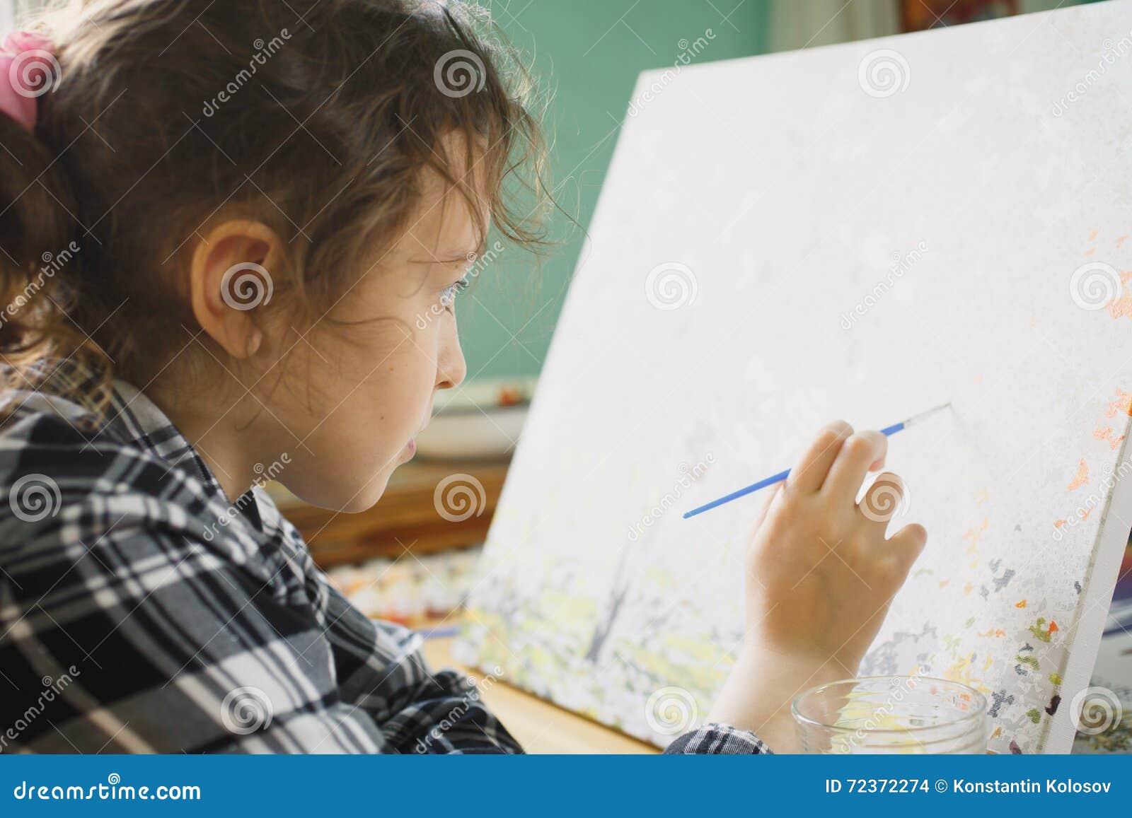 那的女孩与一把刷子的油漆在帆布