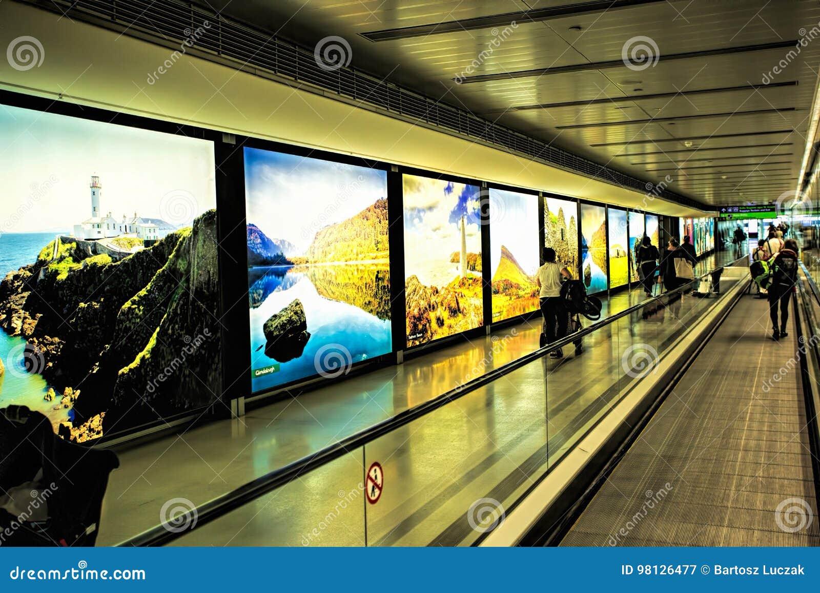 都柏林机场人,旅行带着在走道自动扶梯的手提箱的乘客在与爱尔兰的被突出的图象的行动t的