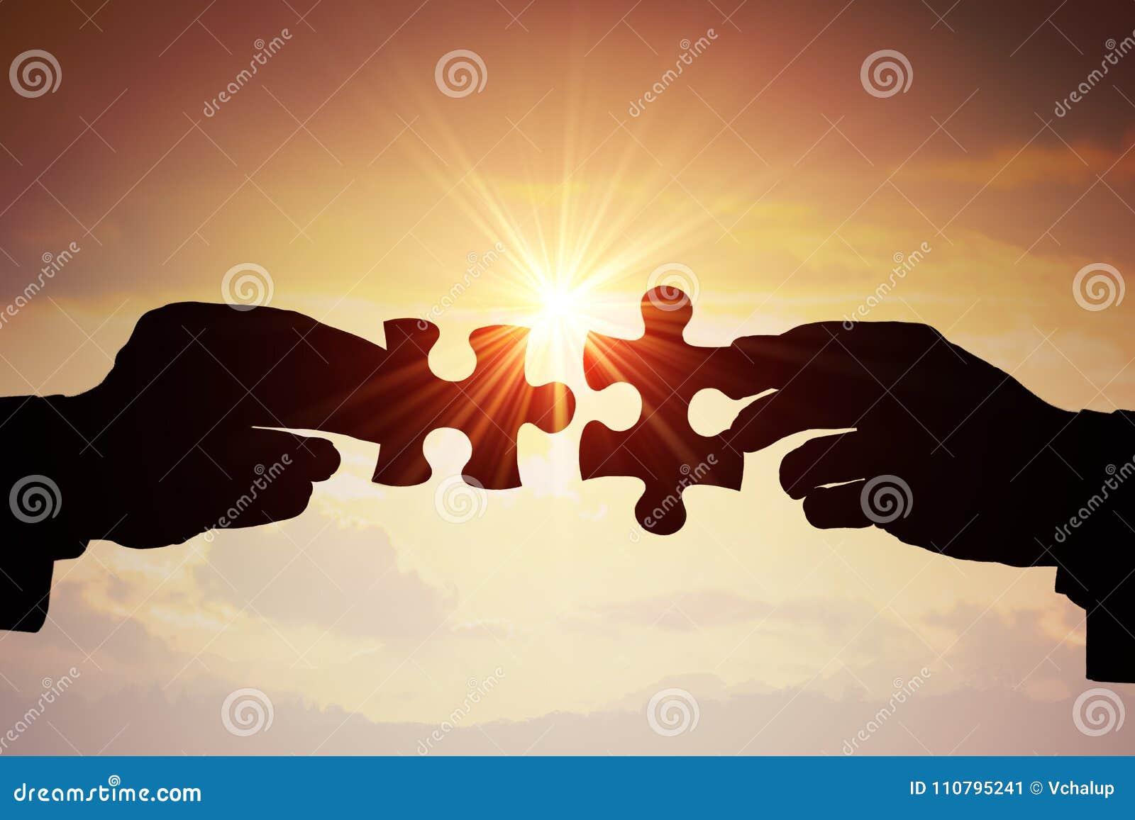 配合、合作和合作概念 一起加入难题的两个片断两只手剪影