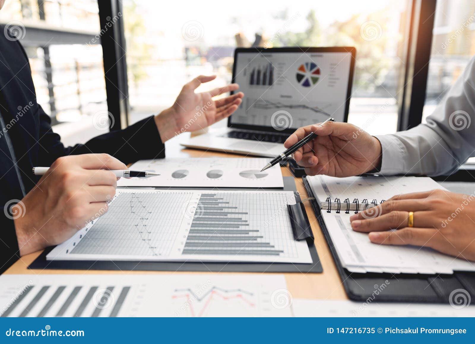 配合公司会议概念,商务伙伴与一起分析起始的财政项目的手提电脑一起使用