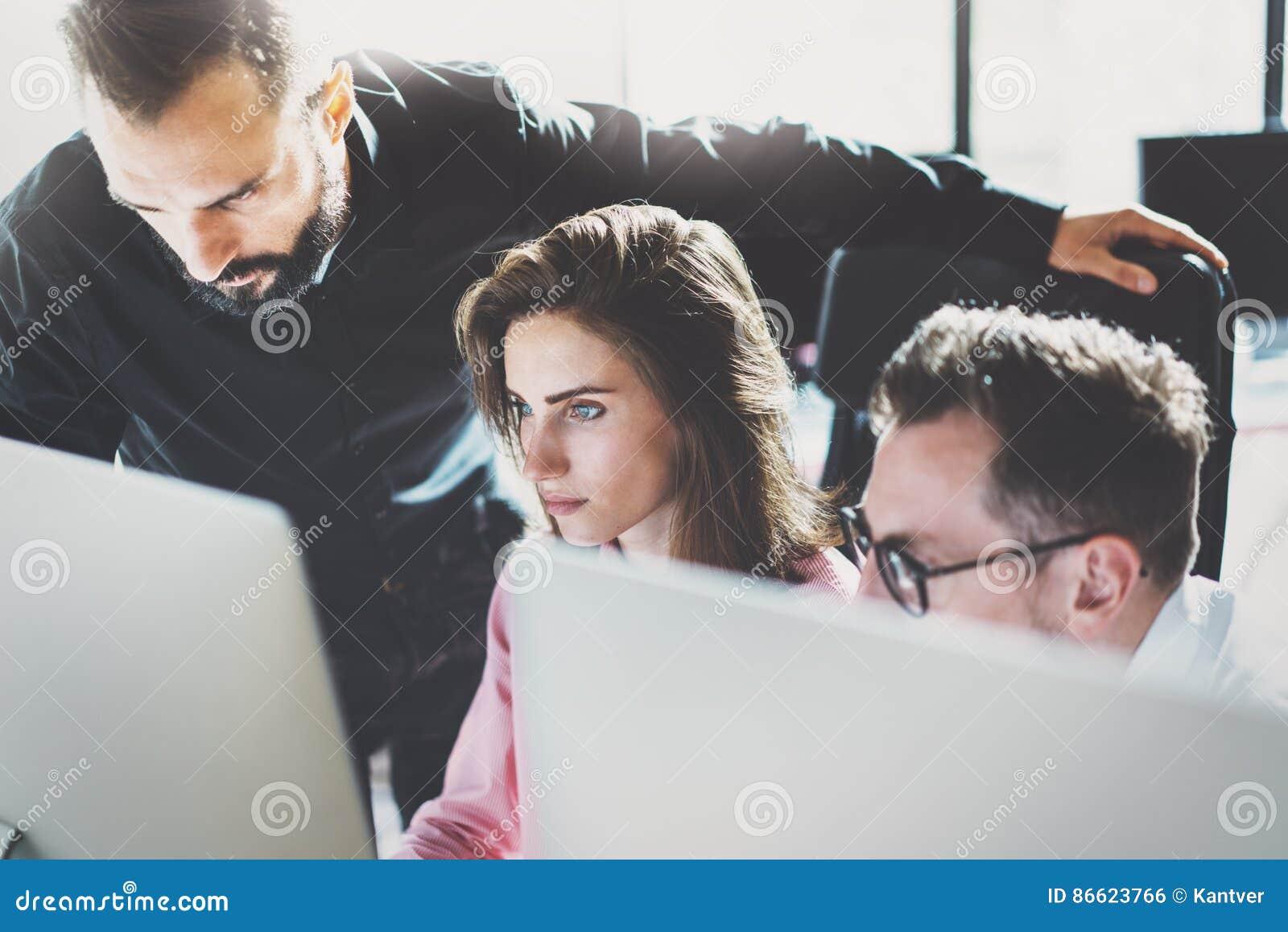 配合概念 年轻工友与新的事务一起使用在现代办公室射出 小组三个人分析数据