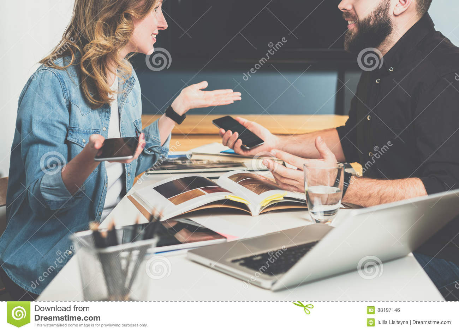 配合,年轻设计师坐在桌上在办公室并且采摘在编目的结束的材料 企业生意人cmputer服务台膝上型计算机会议微笑的联系与使用妇女