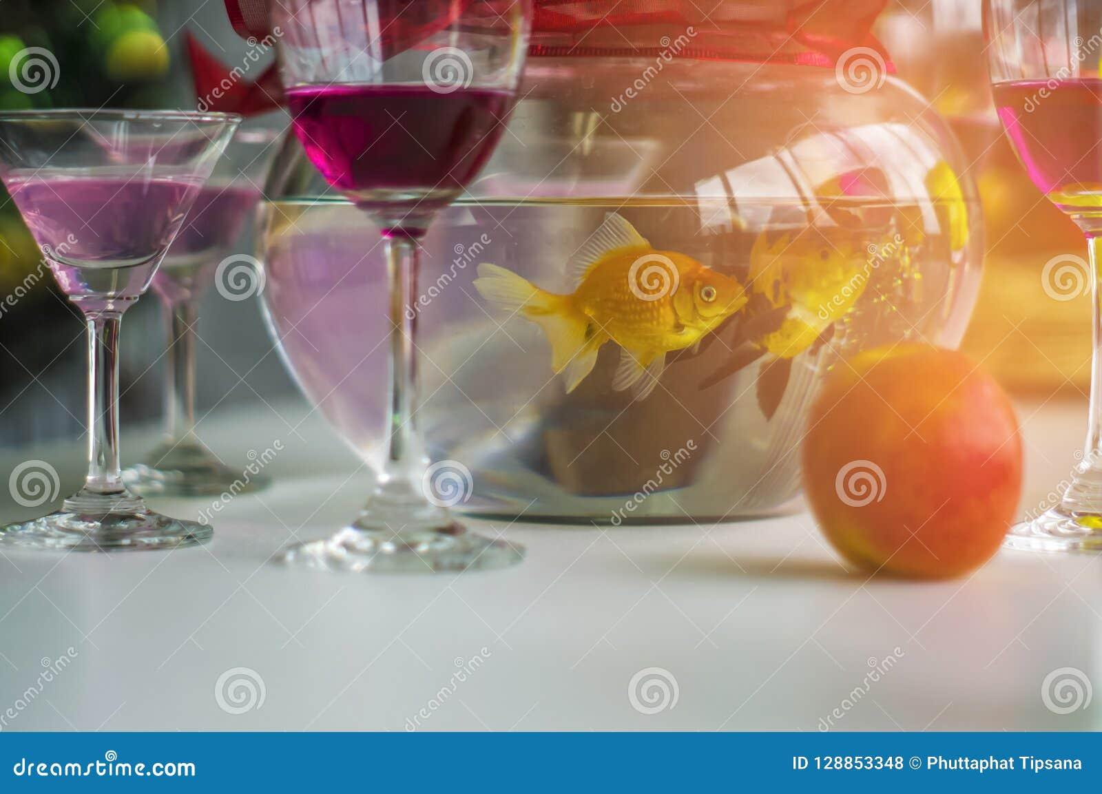 酒杯和鸡尾酒和精神和苹果和金鱼瓶子,投入了一张木桌在圣诞晚会