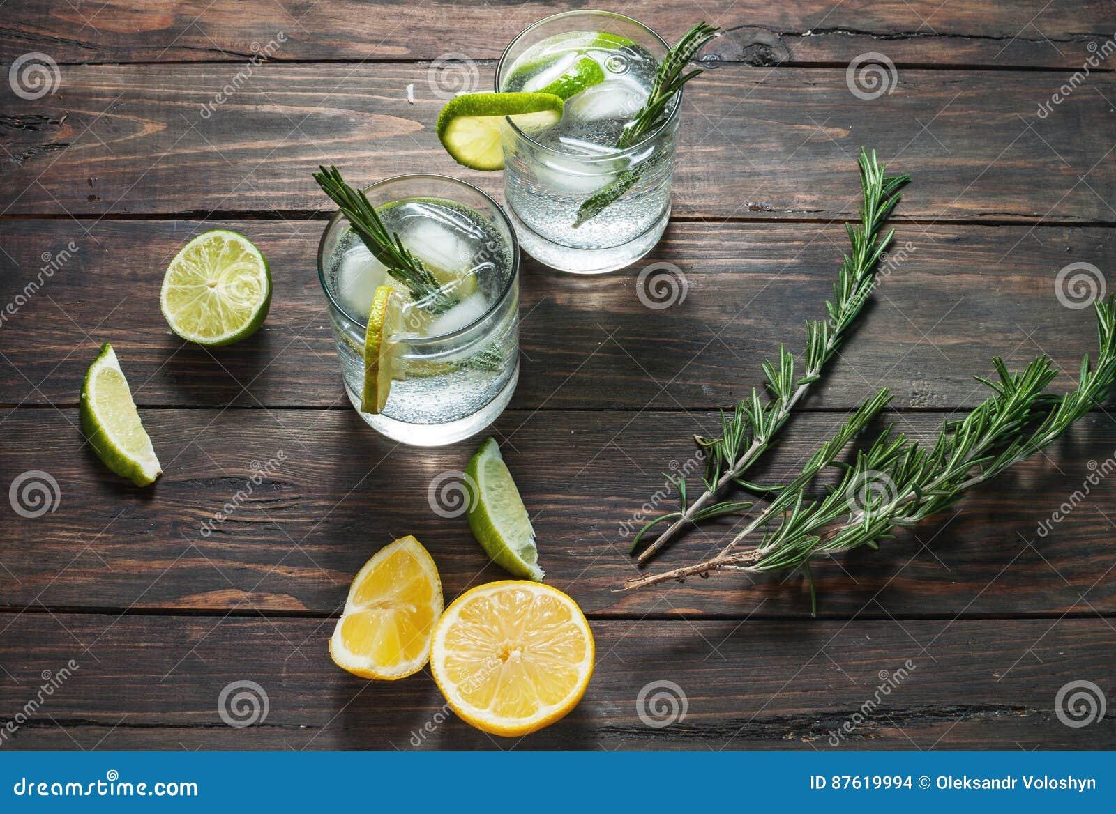酒精饮料杜松子酒补剂鸡尾酒用柠檬、迷迭香和冰在土气木桌上