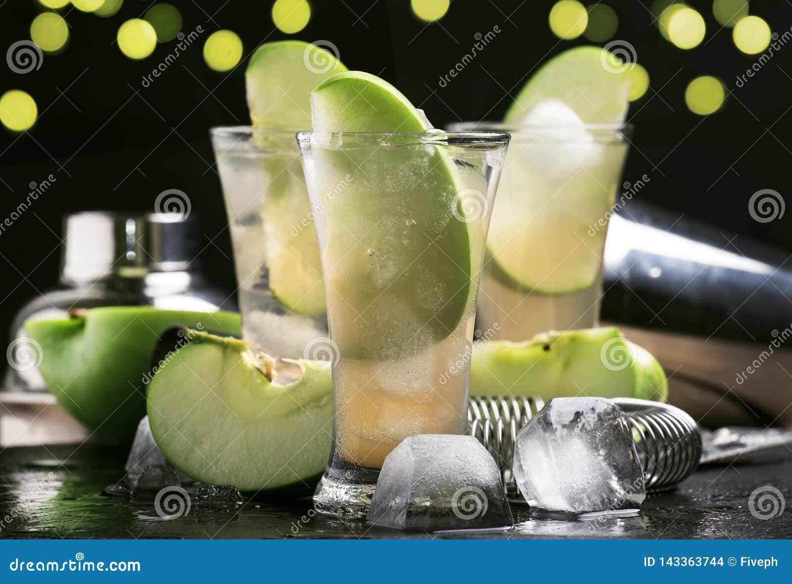 酒精鸡尾酒用干白色苦艾酒、绿色苹果、汁液、苏打和冰,黑酒吧柜台背景,选择聚焦