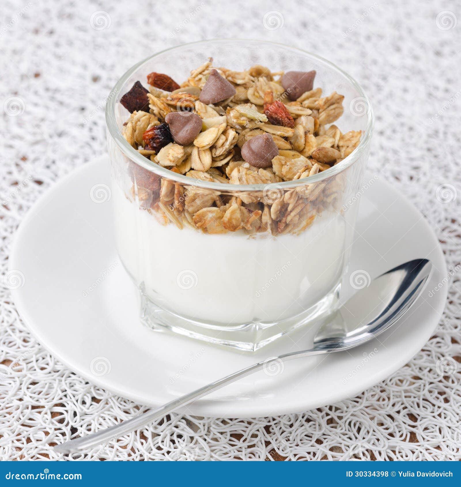 酸奶和格兰诺拉麦片与黑人在一个玻璃烧杯