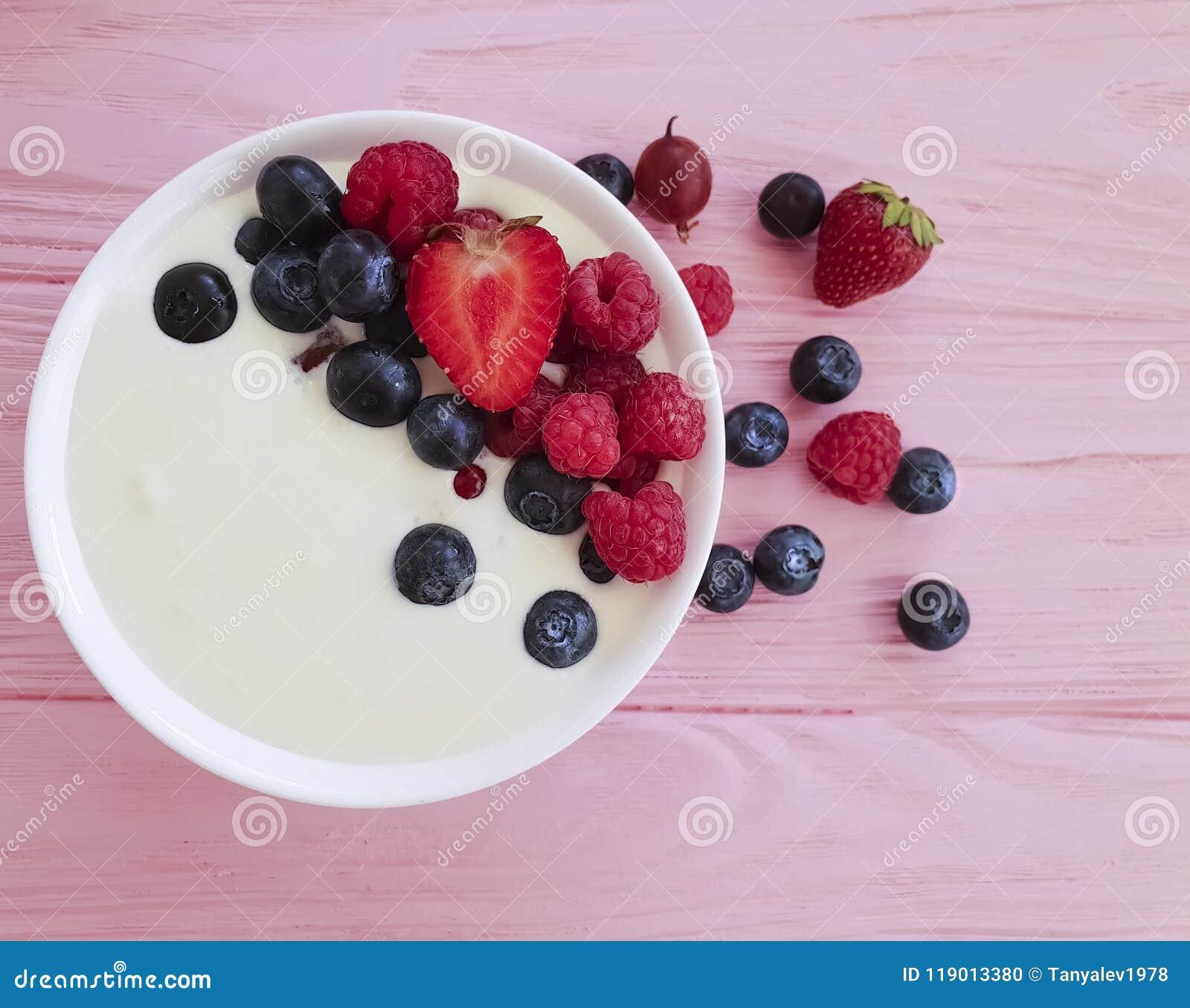 酸奶,草莓,莓,自创自然节食的茶点的蓝莓桃红色木背景,