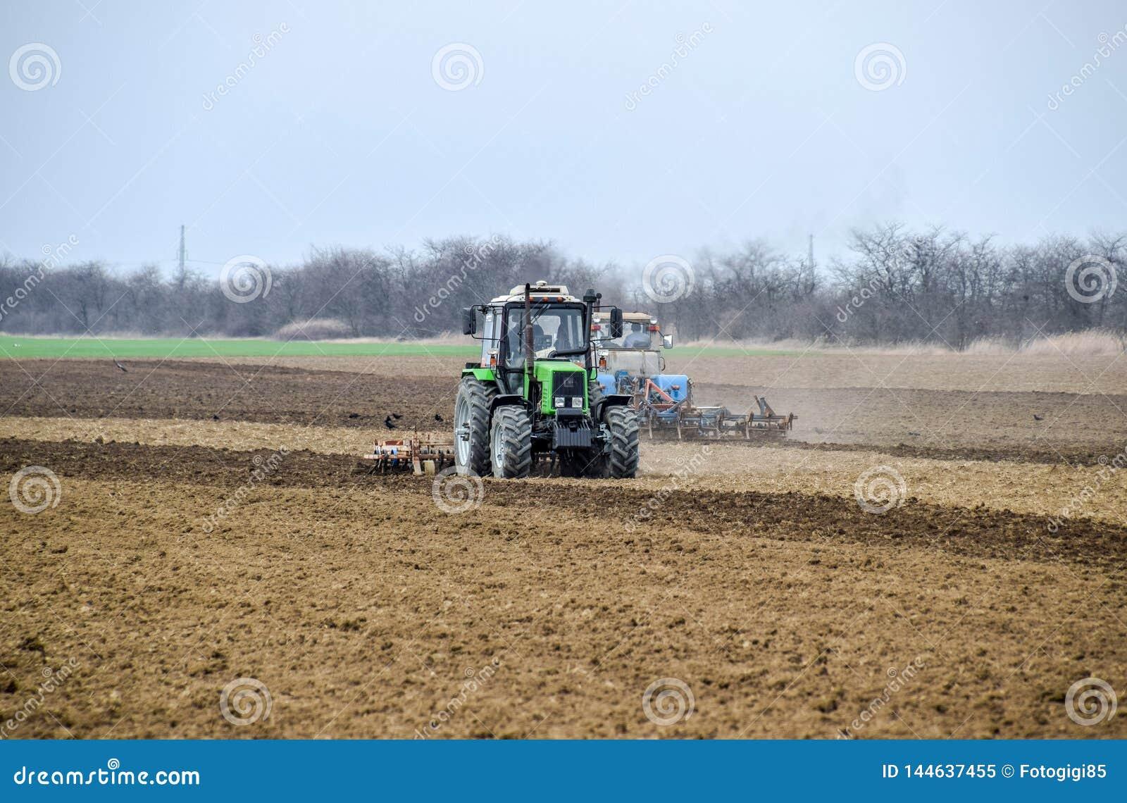 醉汉和在播种前松开在领域的土壤 拖拉机犁与a的一个领域