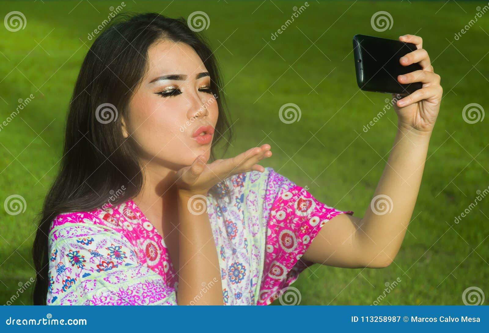 采取与手机照相机的年轻愉快和美丽的亚裔中国妇女selfie pic投掷摆在户外在绿色的亲吻