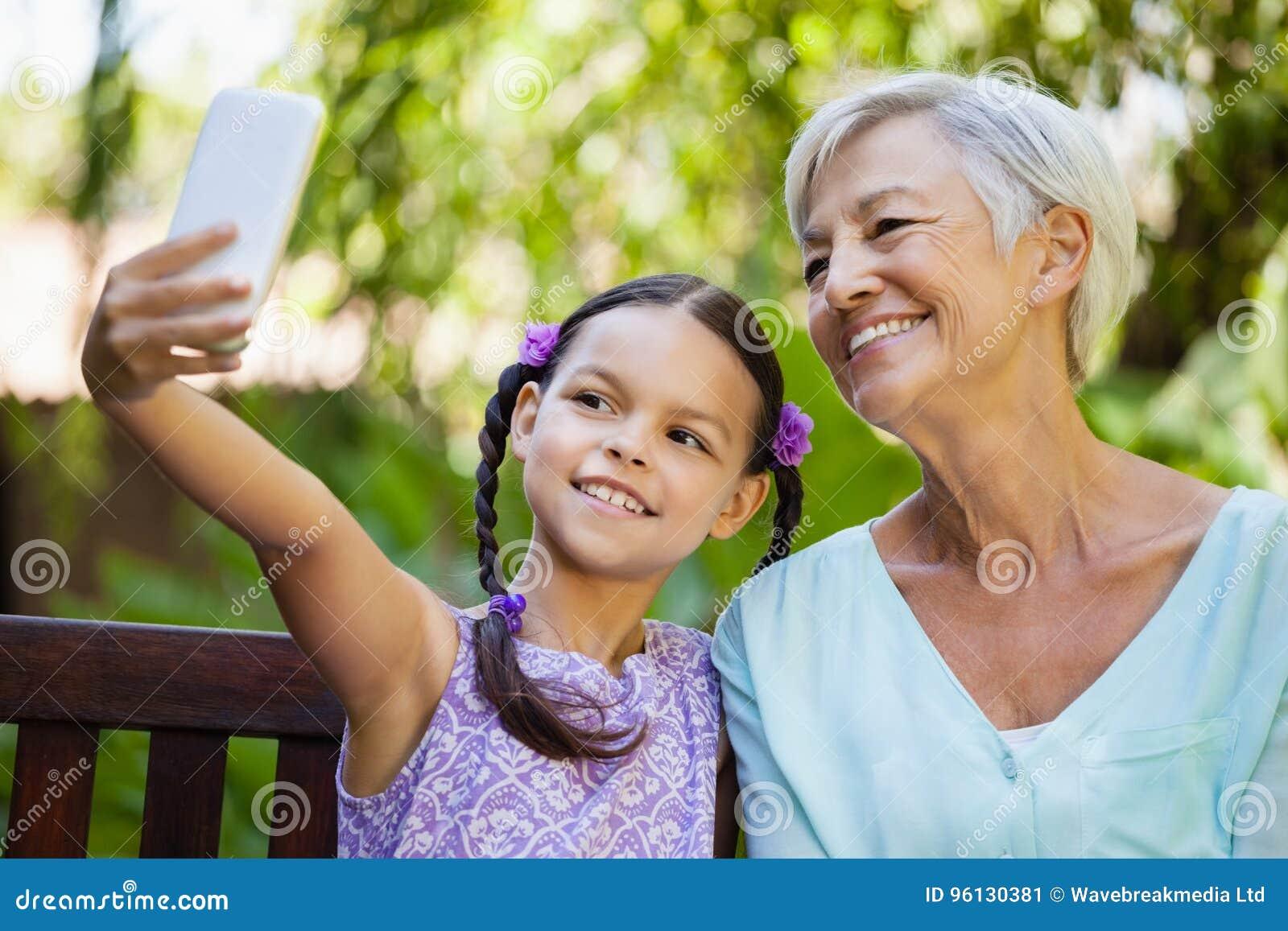 采取与祖母的微笑的女孩selfie