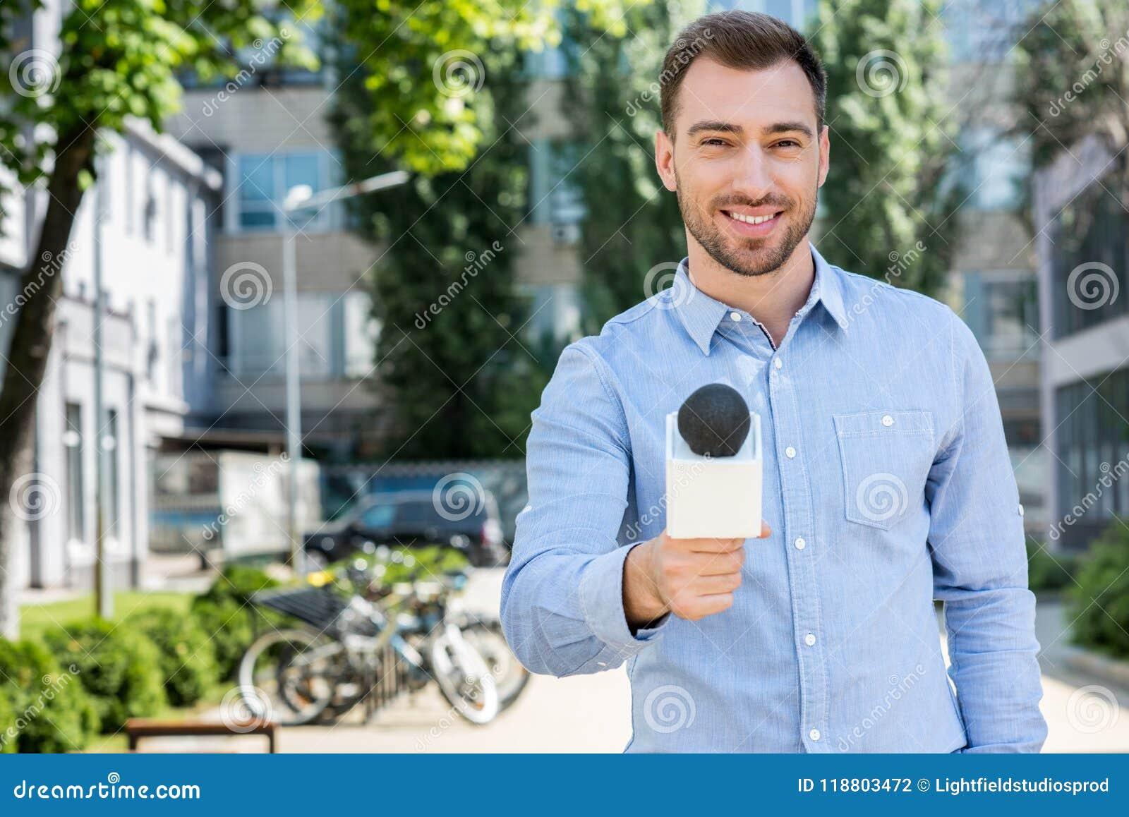 采取与话筒的微笑的男性新闻记者采访
