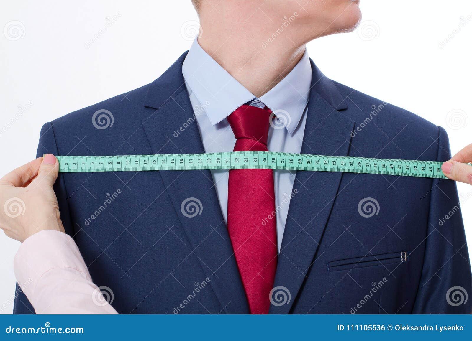 采取企业夹克衣服的裁缝的特写镜头图象测量 在红色领带的商人和在被隔绝的演播室的蓝色衣服