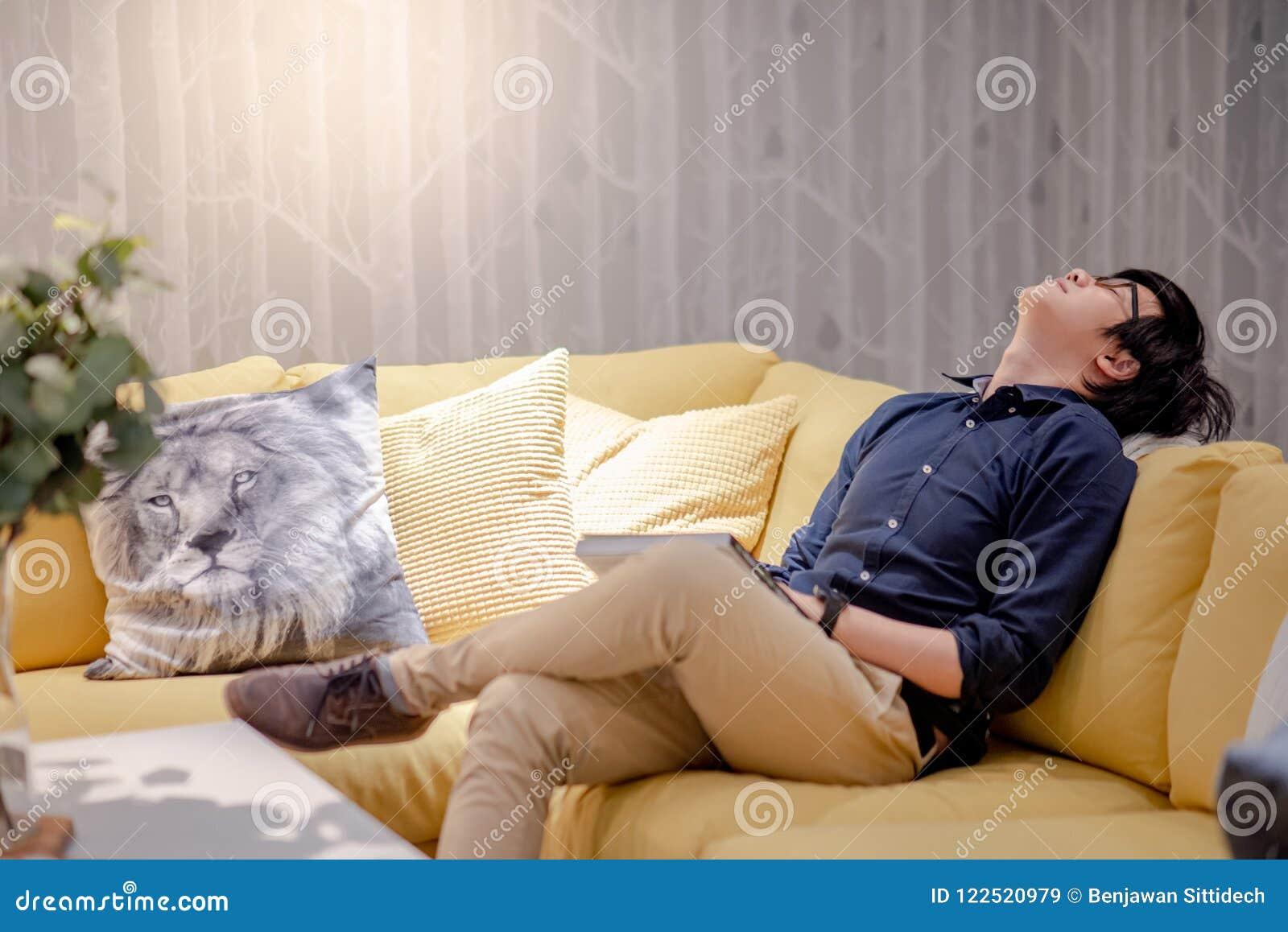 采取休息的年轻亚裔人,当在沙发时的阅读书