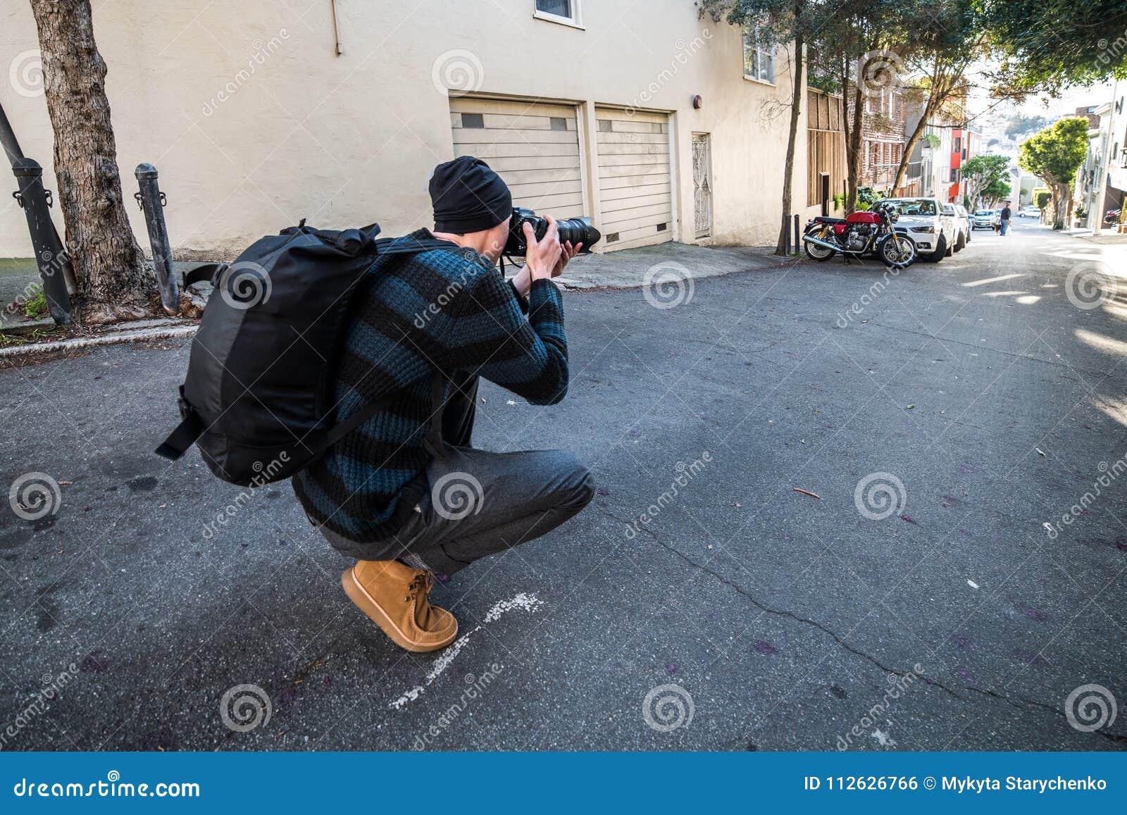 采取图片在他的期间在城市街道上的摄影师旅行