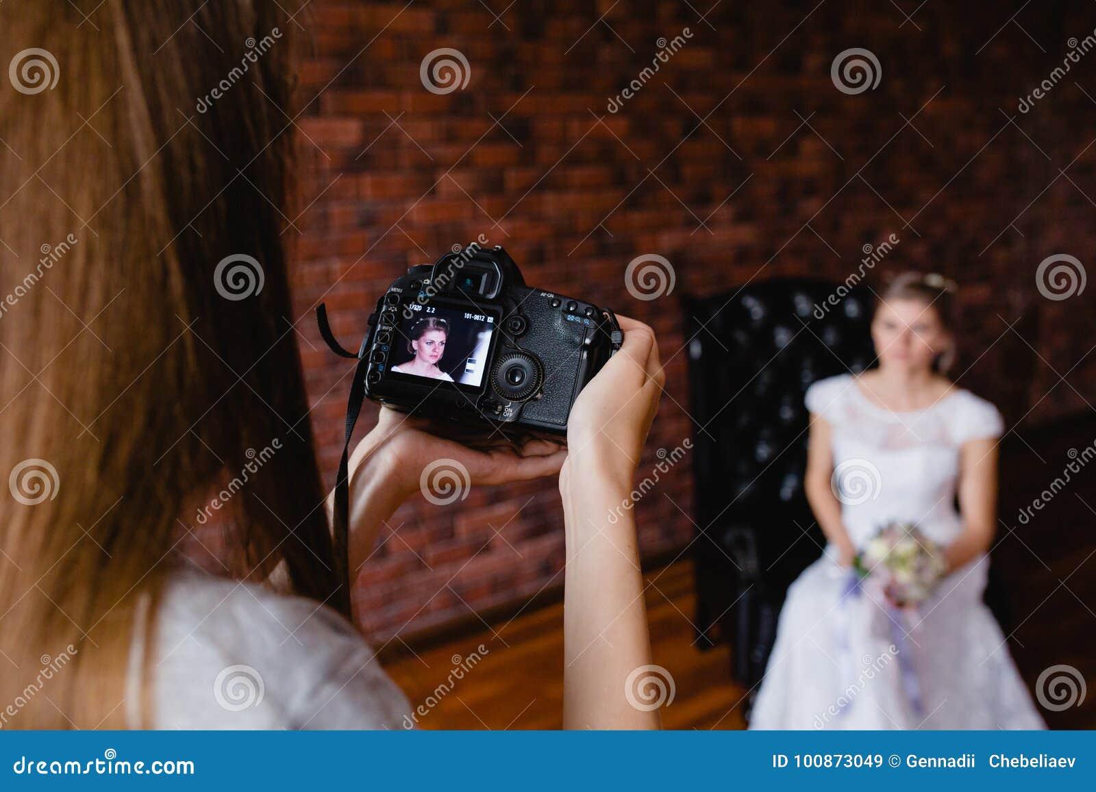 采取图片新娘的摄影师在一把大皮革扶手椅子的演播室