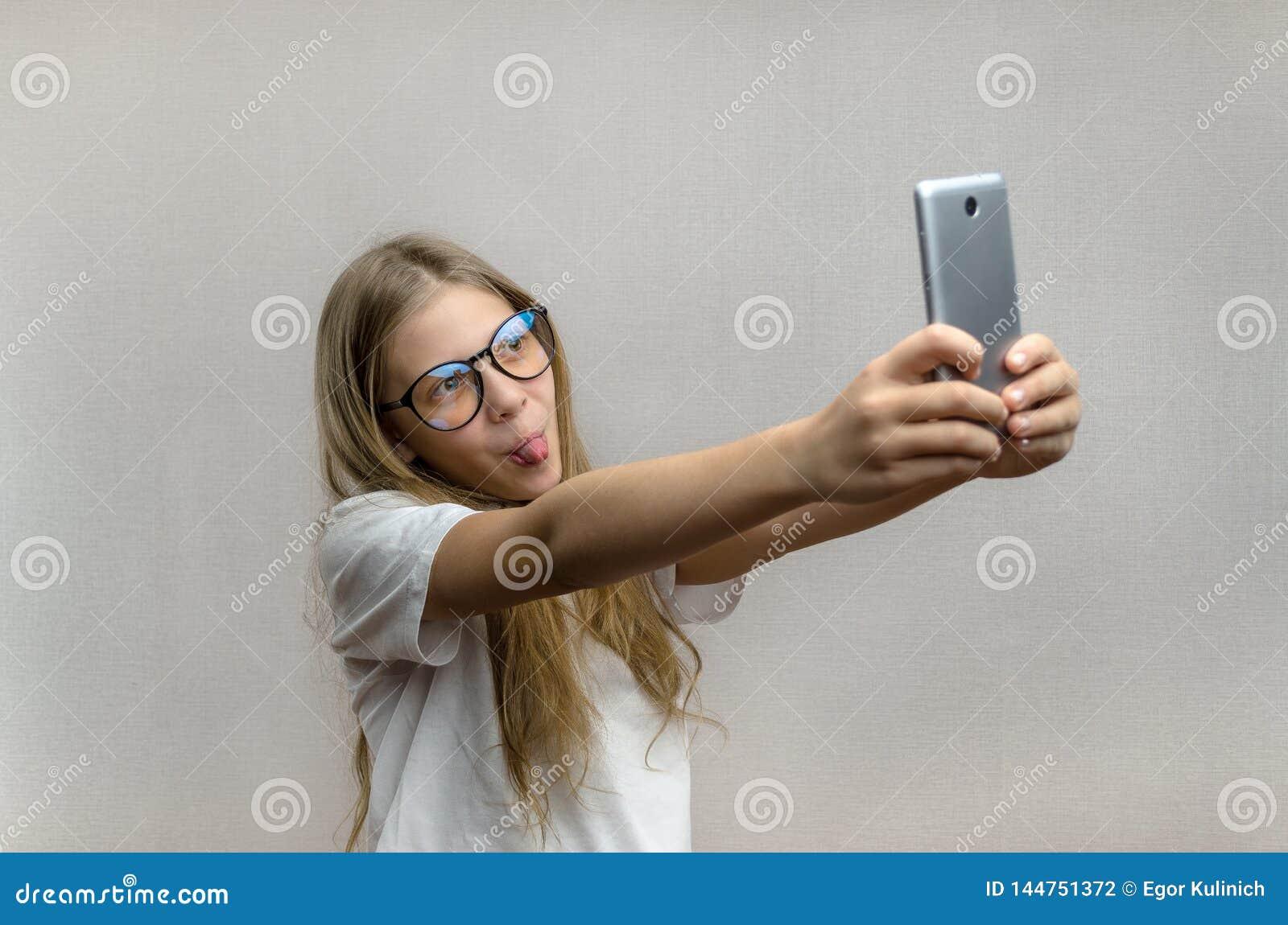 采取在她的智能手机的一selfie一个白肤金发的女孩的画象 r 年轻博客作者